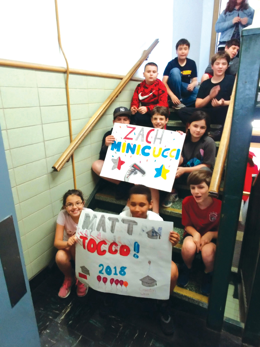 SPECIAL PERSONALIZATION: At several schools, the students had made personalized signs and posters, and they waited for a glimpse of the alumni who had attended there.