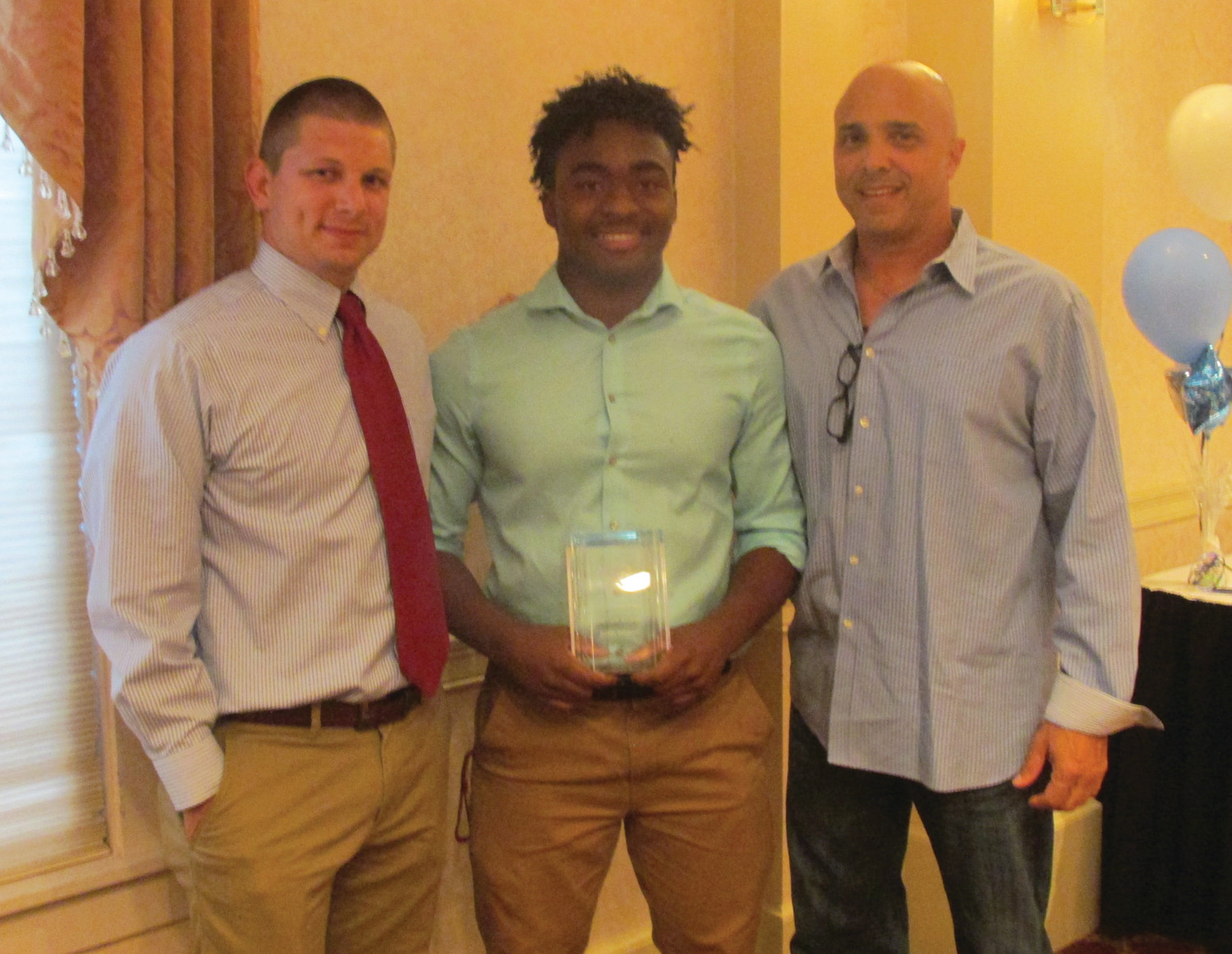 SUPER STAR: Elijah Burgess (center), who Monday night was honored as the JHS Male Athlete of the Year, is joined by wrestling Coach Kevin Sutherland (left) and football coach Joe Acciardo after receiving the coveted honor. (Sun Rise photo by Pete Fontaine)