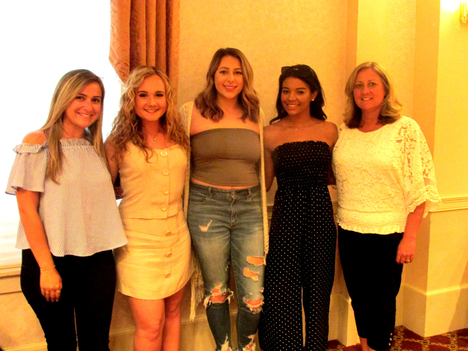 PARILLO'S PACK: Tiffani Parillo (left), assistant cheerleading coach at JHS and her mother Susan Parillo (right), the squad's head coach, join Captain Fallon Davis (second left) who received a scholar-athlete award and four-letter winners Jillian Quick and Daijah Bennet at Monday's special senior sendoff party. (Sun Rise photo by Pete Fontaine)