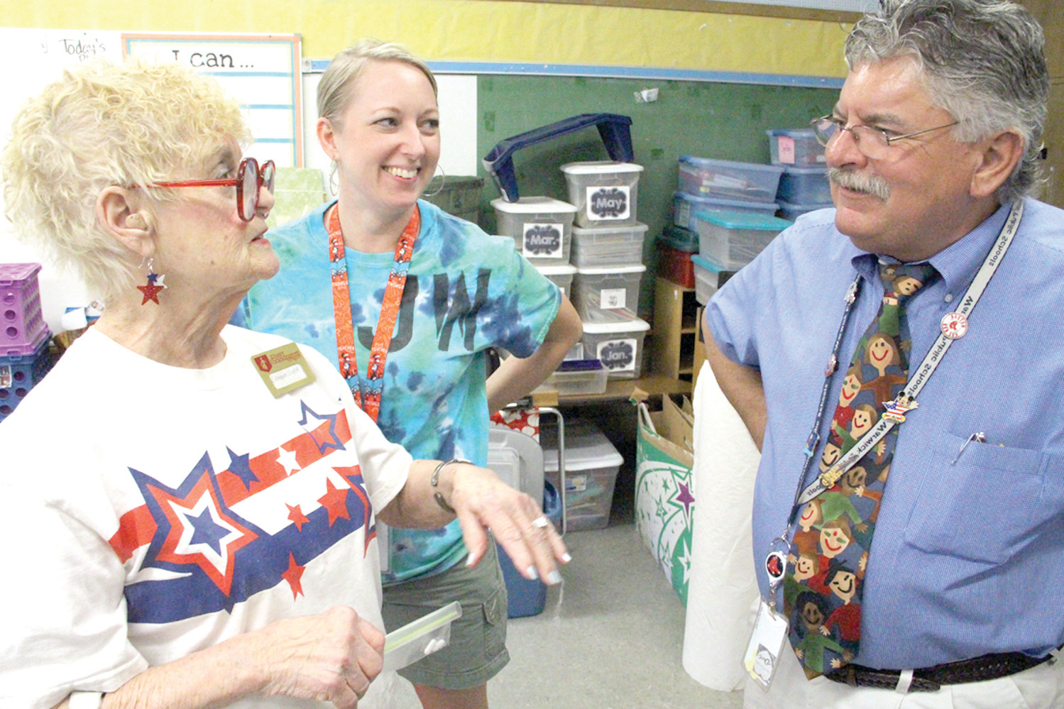 "PARTY GIRL: ""Grandma"" Gloria Walker talks with John Wickes School first grade teacher Jennifer Travison and school Principal Roy Costa at the party she threw Monday at the school."