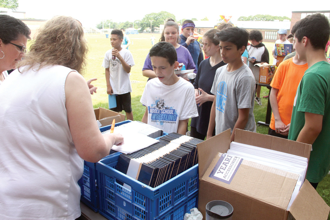 FILLING ORDERS: Michelle Curran, who advised the school's yearbook club, hands out copies. The books that had to be pre-ordered cost $36 for a hardcover copy and $30 for a soft copy. For the first time, Curran provided at no charge memento autograph books to the students.