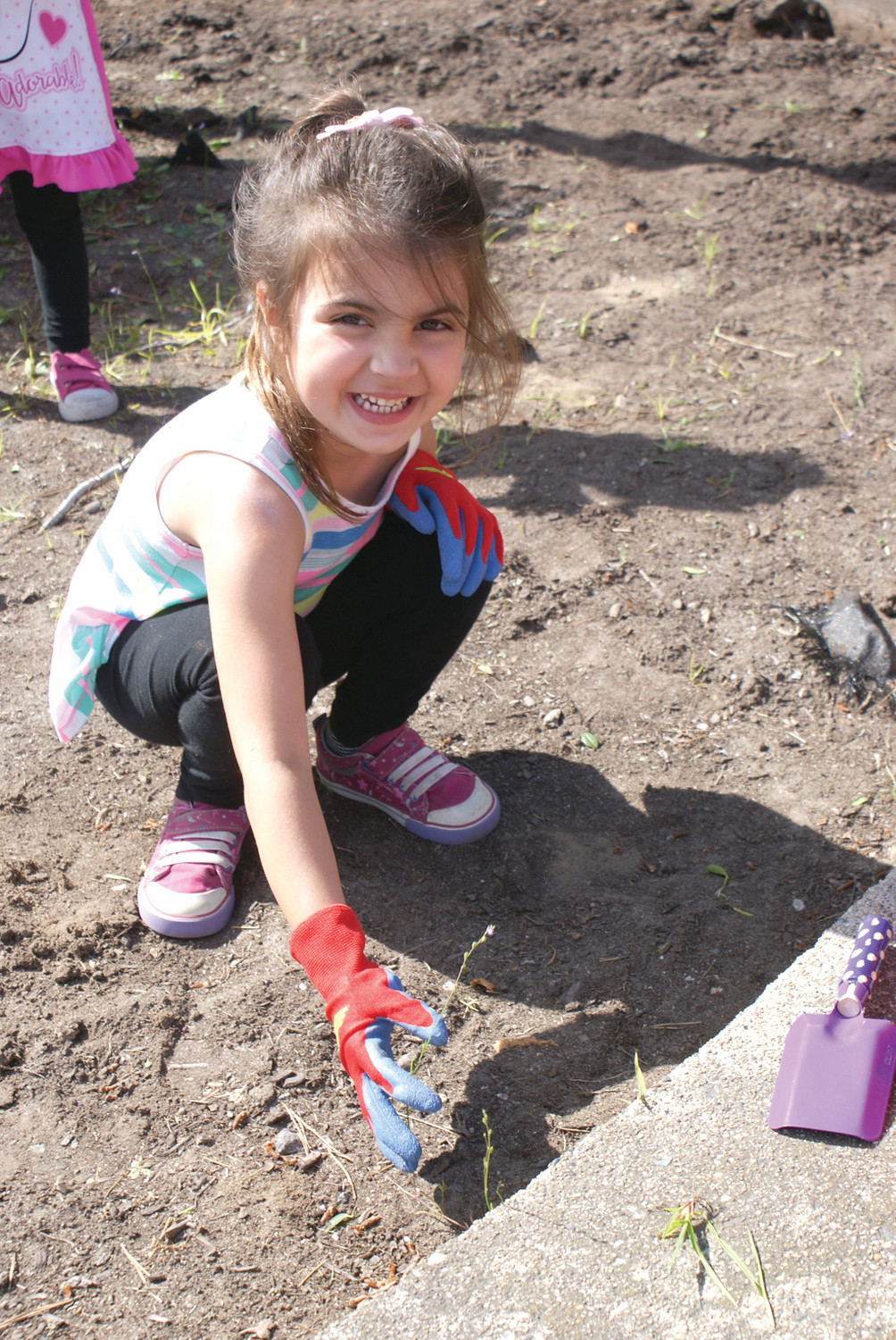 NEVER TOO YOUNG: One of the younger volunteers at the Ward 5 Beautification Project was Annie Agresti, age 4, working at pulling weeds at Sivo Park on Florida Ave.
