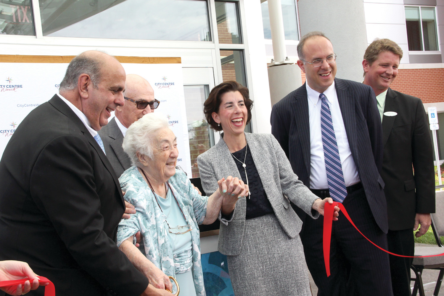 LEAVE IT TO MOM: Michael D'Ambra called on his mother, Sue, to wield the scissors and cut the ribbon held by Mayor Joseph Solomon and Gov. Gina Raimondo to open the Hyatt Place Hotel.
