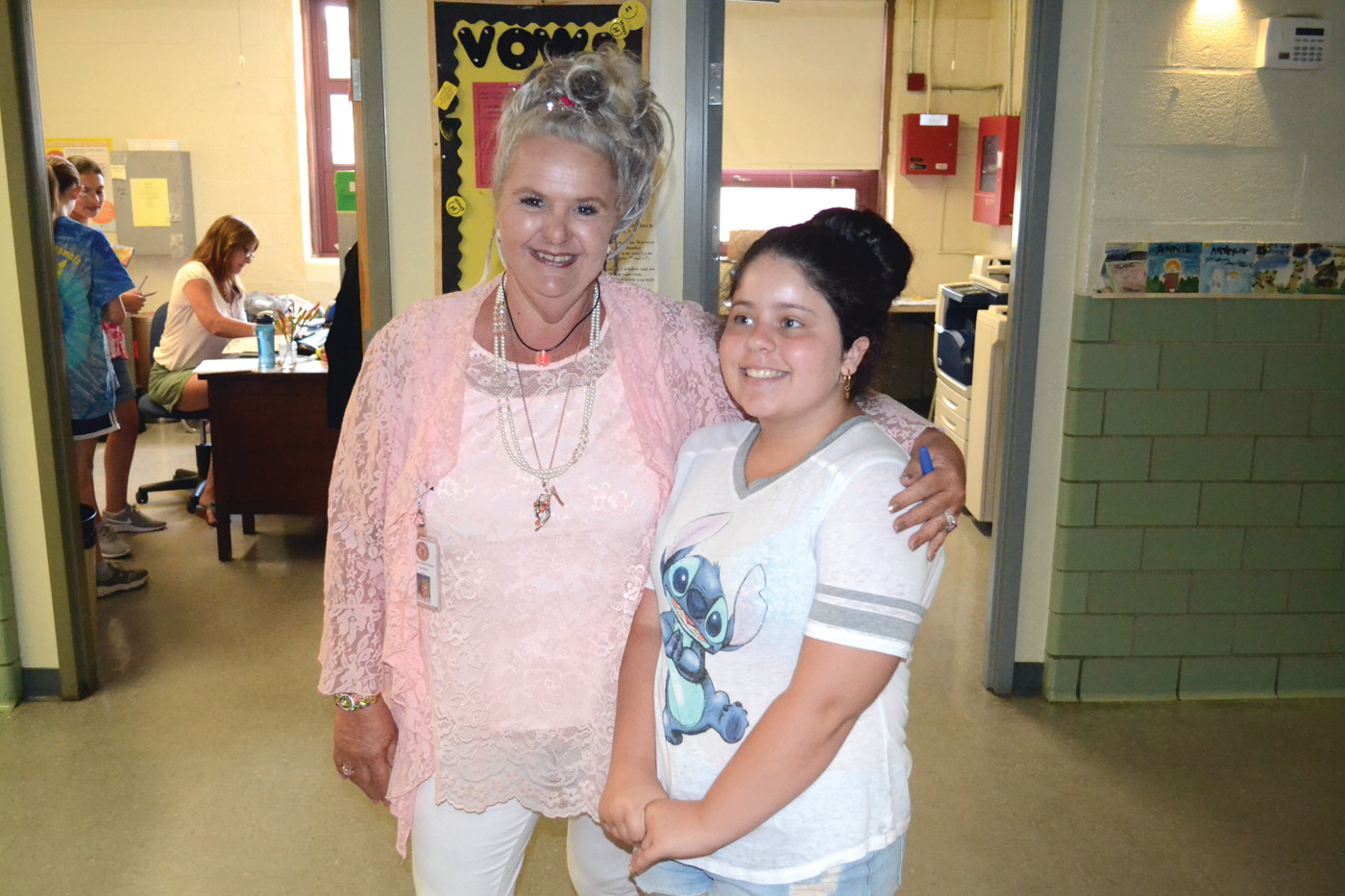 FAREWELL TO FRIENDS: Debra Norman, school secretary of nearly 30 years, and student Sabrina Torres shared an embrace on John Brown Francis's final day.