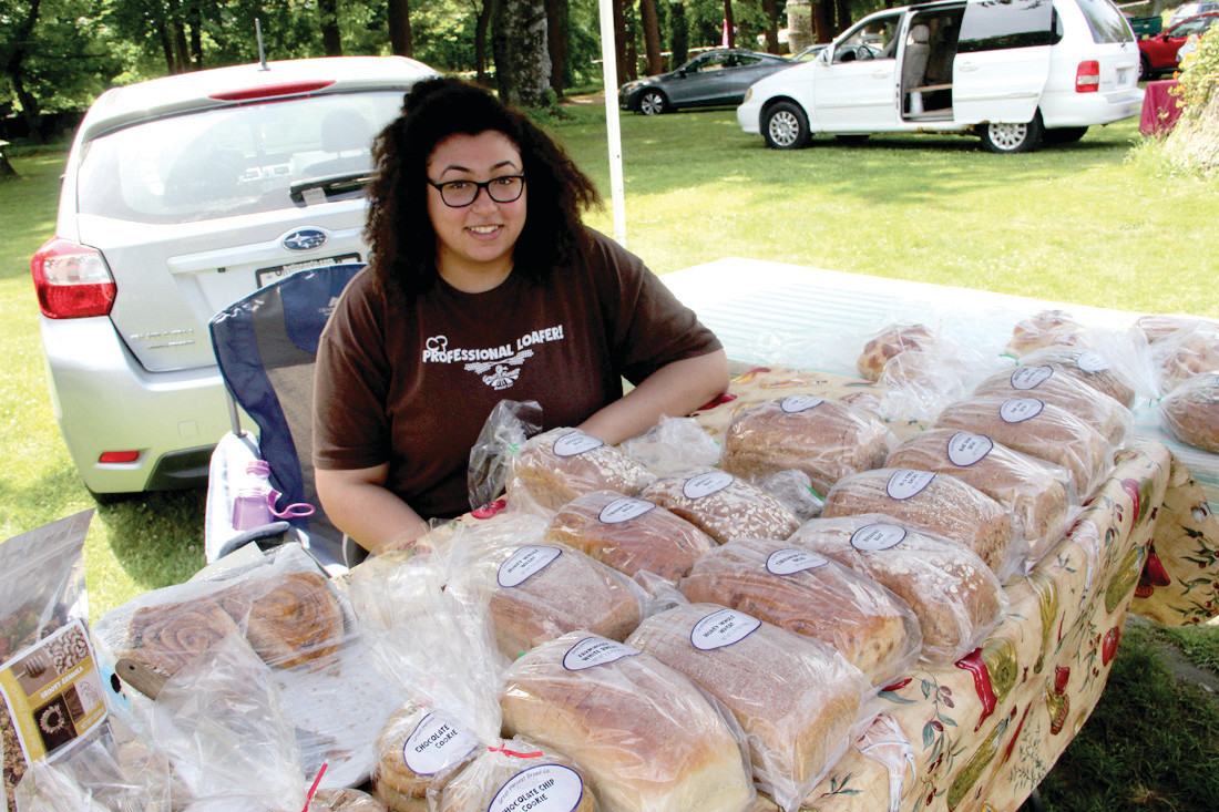 IT GOES QUICKLY: Gia Yarn tends the display of breads offered by Great Harvest from North Kingstown at the Goddard Park market. She said customers have their favorites and if they don't get there early they can be out of luck. (Beacon Communications photos)