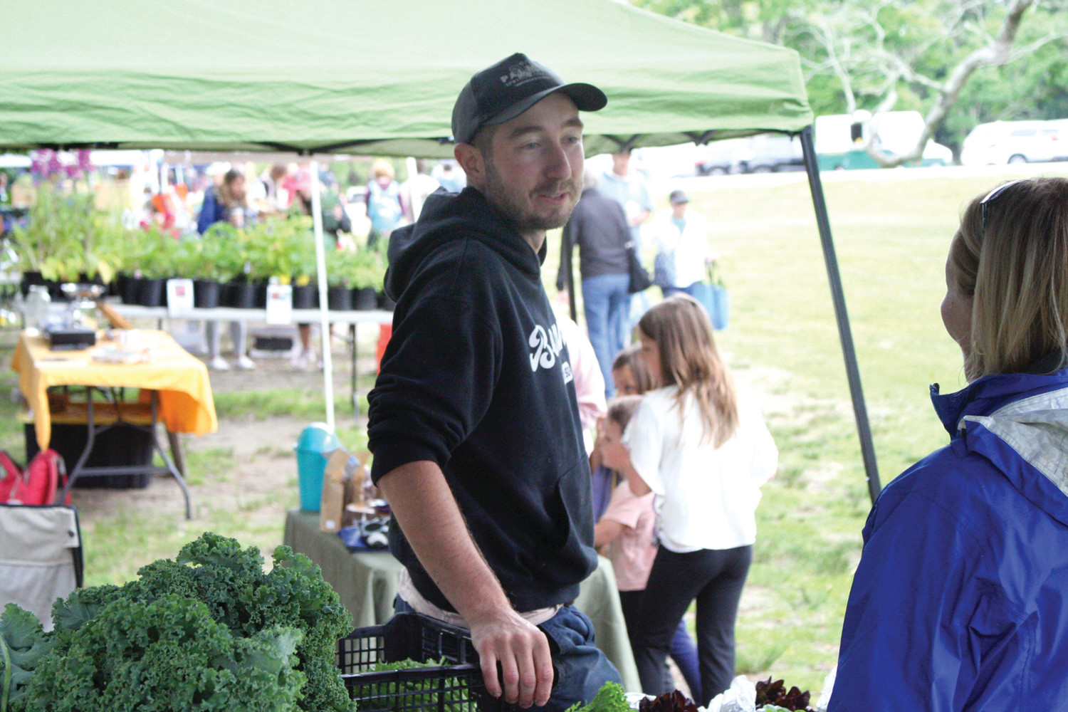 "HOW MAY I HELP YOU: Chris Ryan, a private farmer who sells mostly vegetables at the state farmers' markets, talks to a customer about what type of ""choots"" to buy on Friday at Goddard Park in East Greenwich."