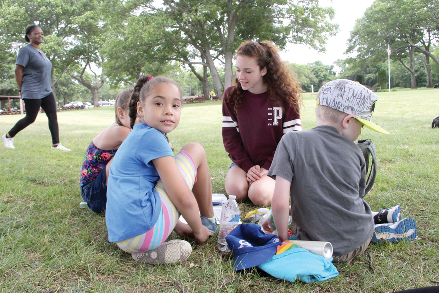 KEEPING TRACK: Junior counselor Myah Cole reviews the camp schedule with her group before the activity stations rotate.