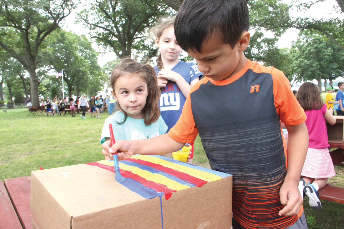 ARTS AND CRAFTS: At the imagination station, a group of campers get creative by constructing totem poles out of cardboard boxes and art supplies. From left, Bianca Aguiar, Amity Hults and Jon Madden.