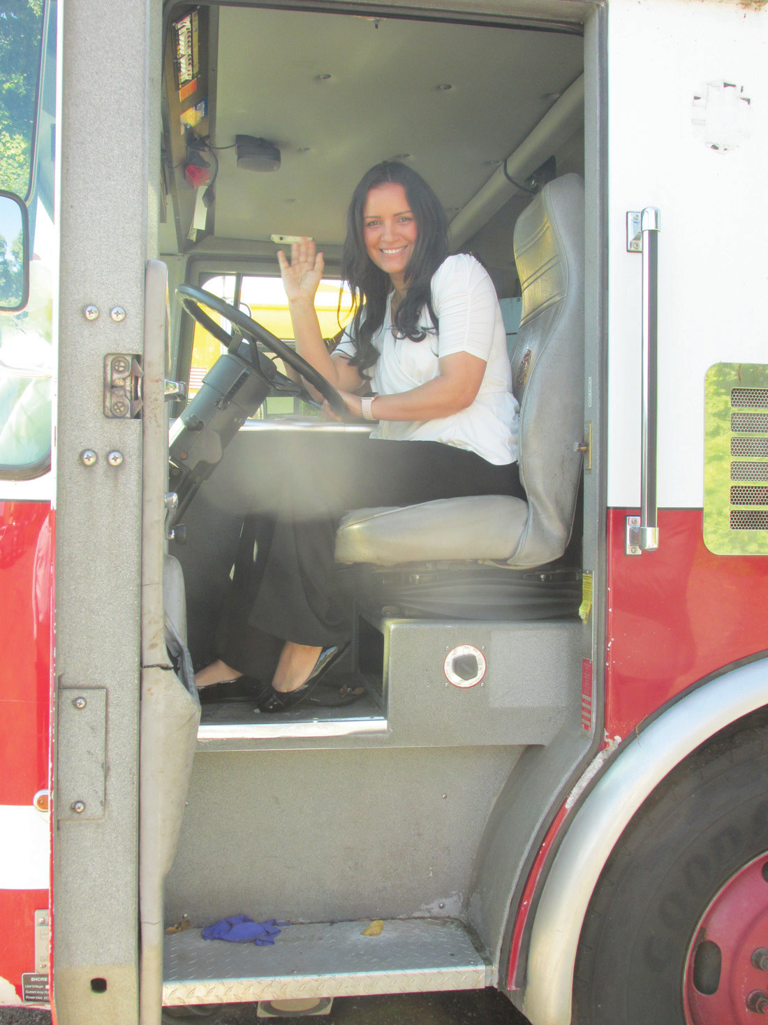 CAROL'S CONNECTION: Community Angels leader Carol Aguasvivas shows her emotions – and smiles – while sitting in this 1999 shiny pumper that helped save lives in Johnston but will soon be dong the same thing in her native village of Bani in the Dominican Republic.