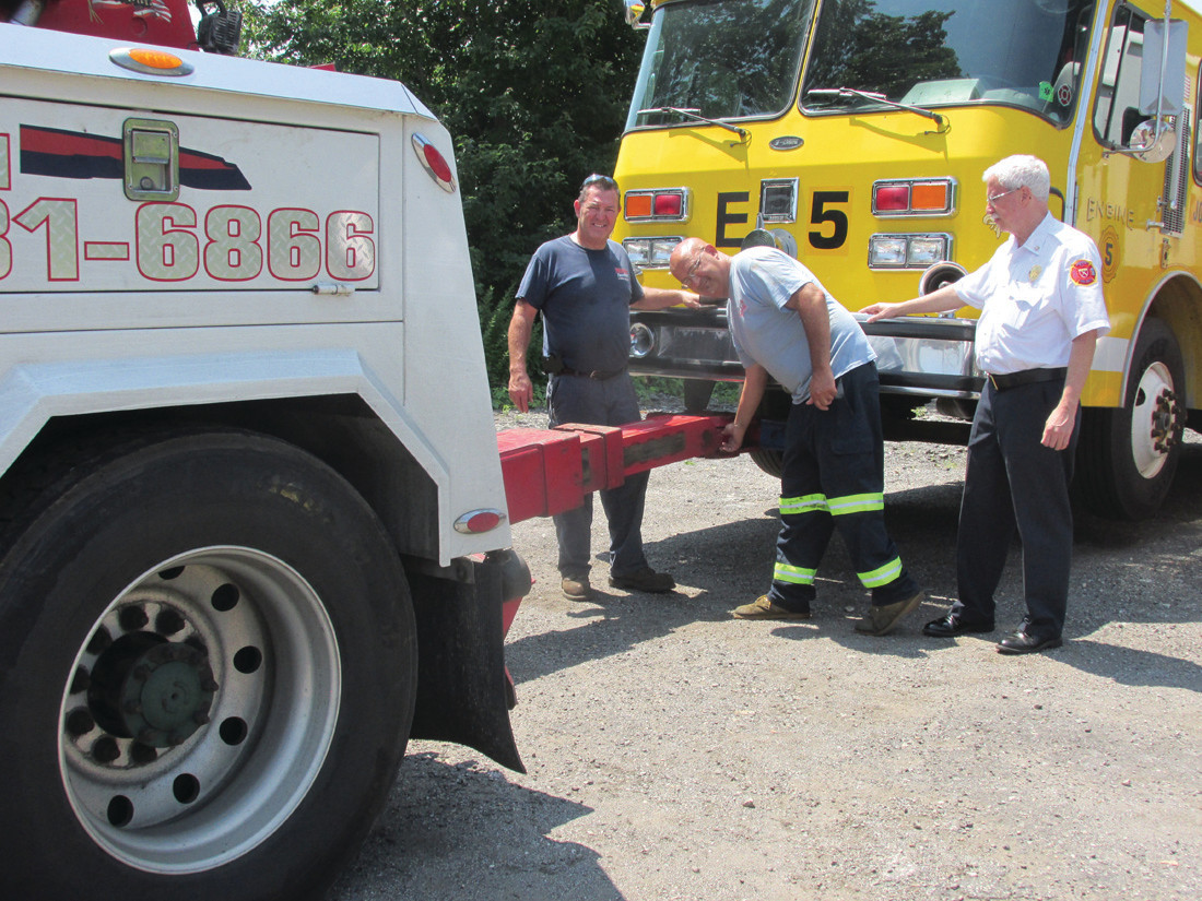 HELPING HANDS: Chris Branch (middle), and his brother Richard who own and operate Precision Towing in Johnston, are set to tow these two fire trucks to Providence where they'll being a 45-day trip to the Dominican Republic that was made possible by Mayor Joseph Polisena's Surplus Donation Program. Looking on is JFD Chief Peter Lamb.