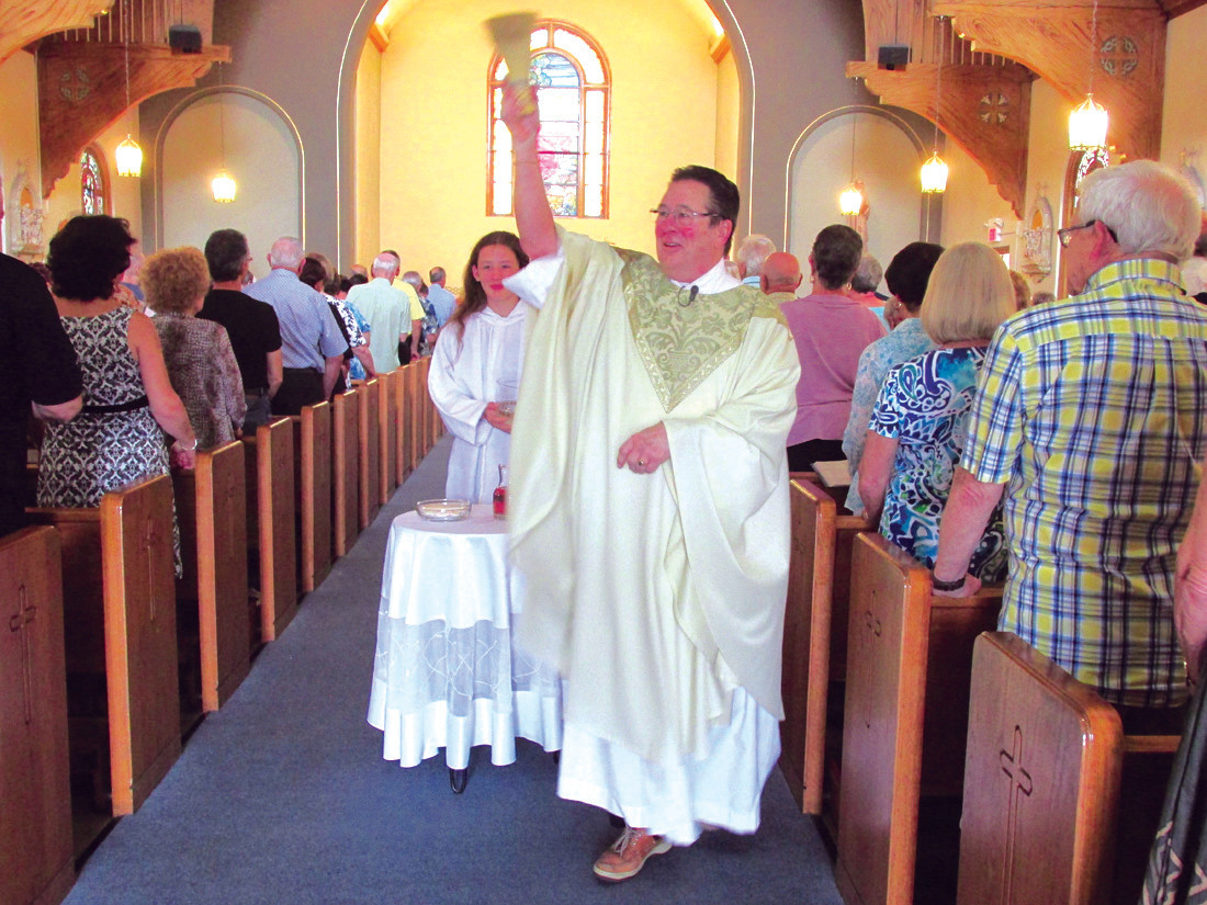 FATHER'S FINALE: Rev. Robert Rochon offers the renewal of baptismal vows and blessing of the holy water during his final mass Sunday at St. Brigid's Church in Johnston. (Sun Rise photos by Pete Fontaine)