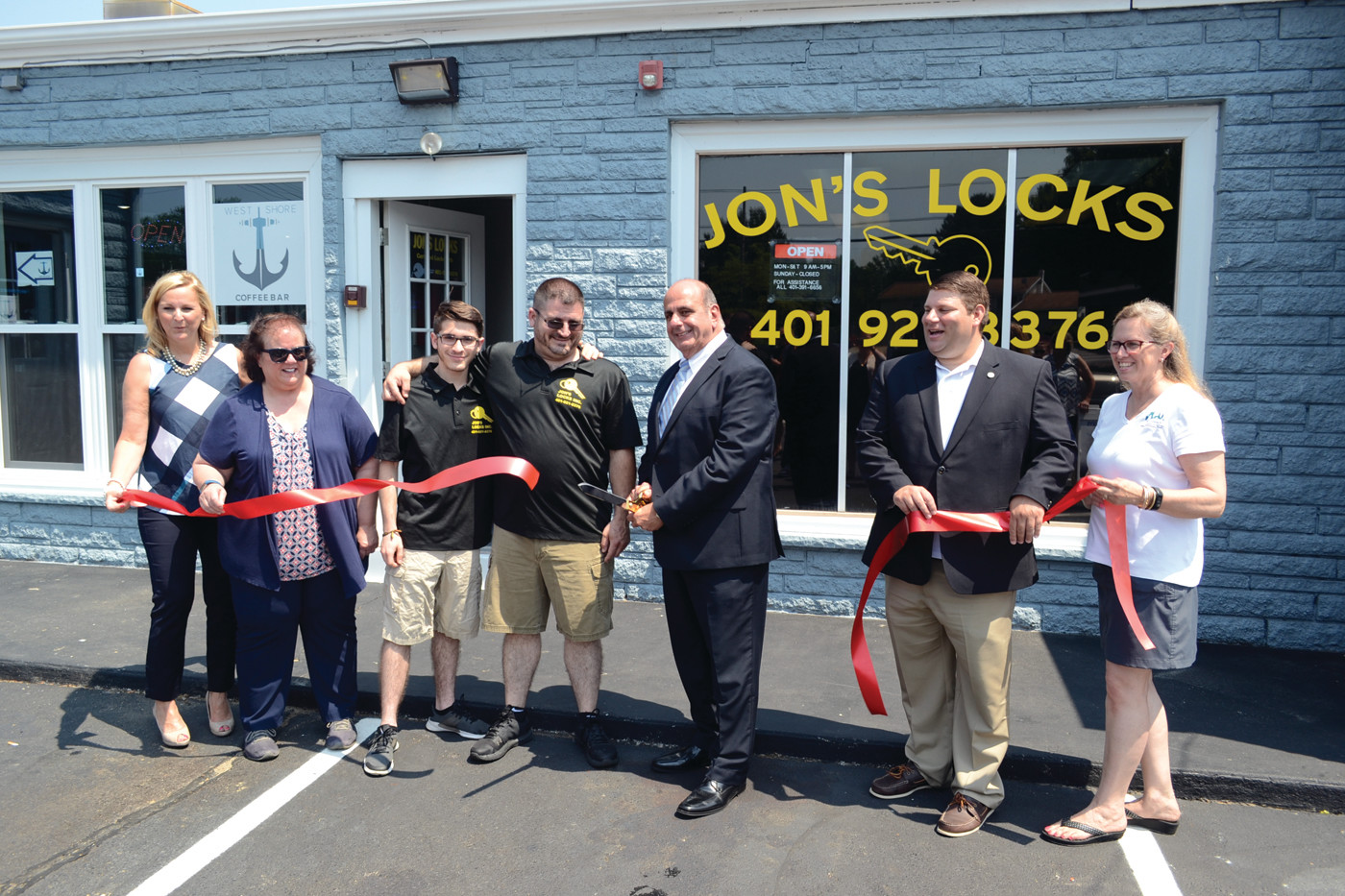 TWO FOR ONE SPECIAL: From left to right, Karen Jedson, Rep. Camille Vella-Wilkinson, Zachary Issa, Jonathan Issa, Mayor Joseph Solomon, Ward 7 Councilman Stephen McAllister and Lauren Slocum cut the ribbon for Jon's Locks.