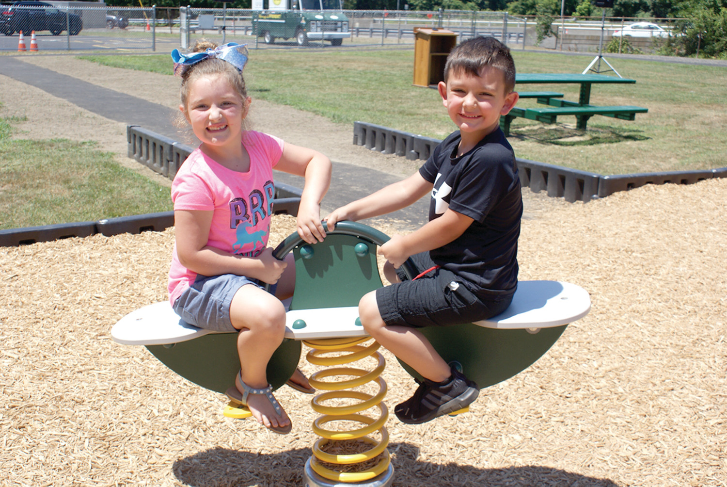 Six year-old Sophia Manna and her four year-old brother Luca play on the see-saw.
