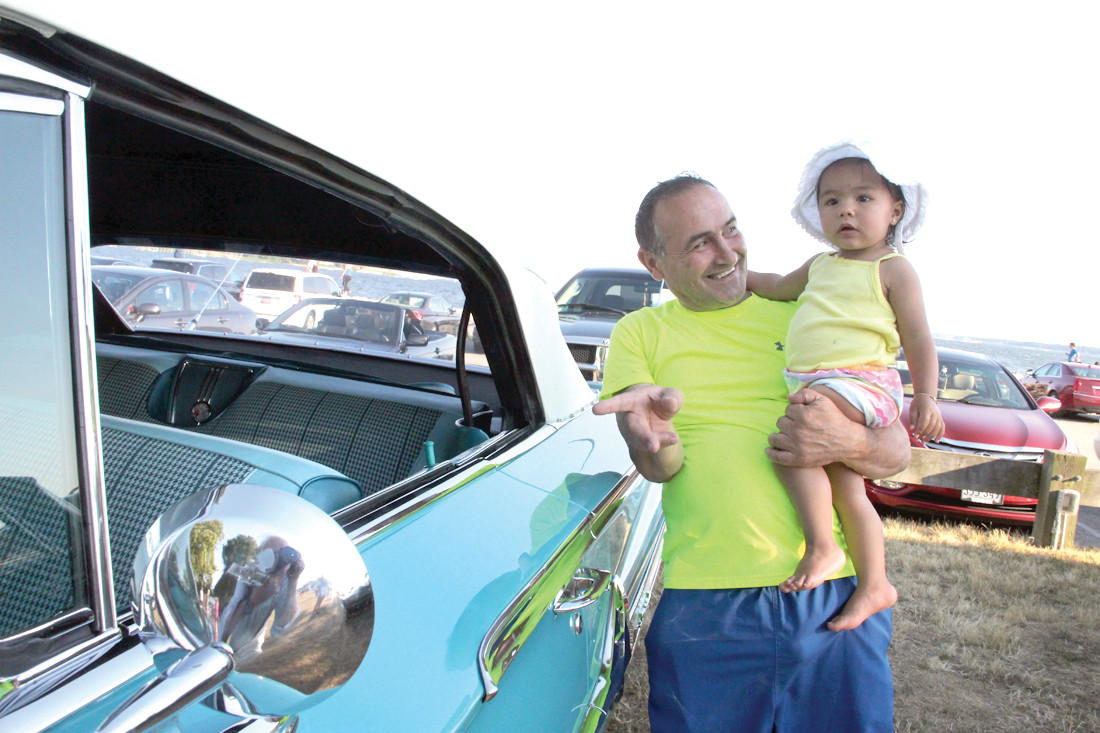 SHE LIKES IT: Manny Teixeira cradles his granddaughter, Kendriana Sebastian, while making the rounds during Tuesday's cruise night. He said she picked out several favorite cars.