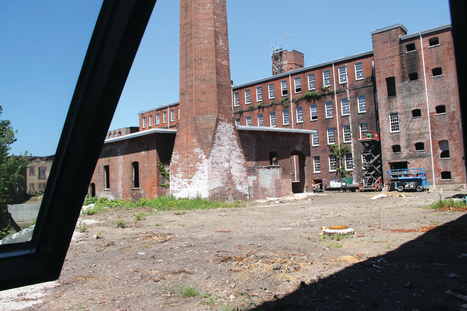SOME CLEANUP REQUIRED: A courtyard at the Pontiac Mills property provides a rear view of a building on Knight Street. The mill property affords the opportunity for several different types of buildings. This smaller building here could perhaps become an office for rentals, of which there should be many, as the complex will eventually have 137 rental units.