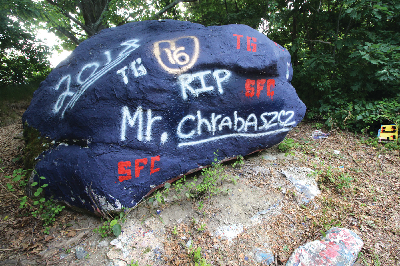 "BIG BLUE ROCK: ""The Rock"" which once served as a memorial to Principal Stephen Chrabaszcz was painted over in school colors by the administration, only to be spray painted by students back to its former purpose."