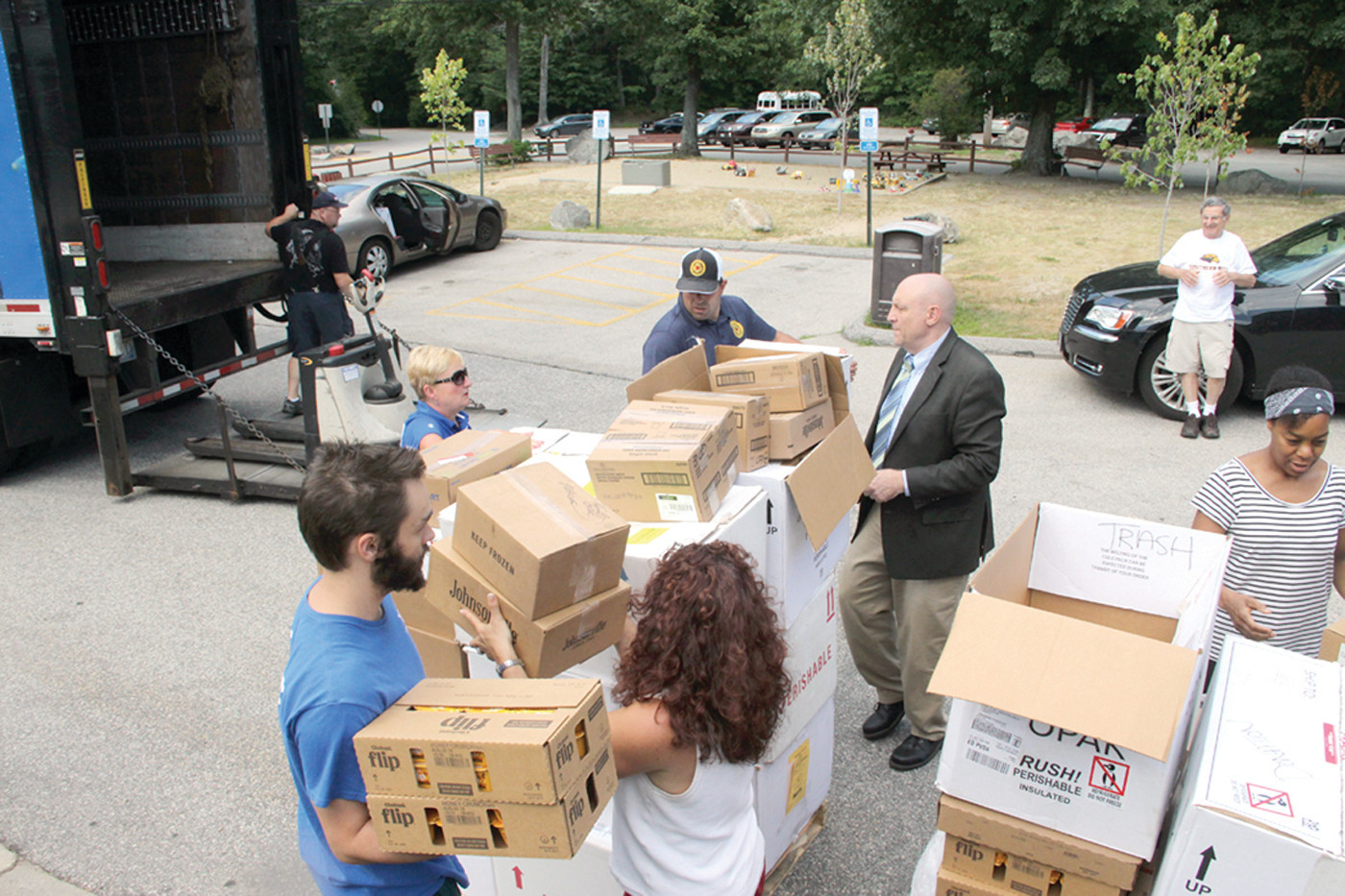 MANY HANDS MAKE LIGHT WORK: Members of area food pantries assisted by Y staff and off-duty firefighters offloaded the food that was delivered to the Y by the Teamsters.