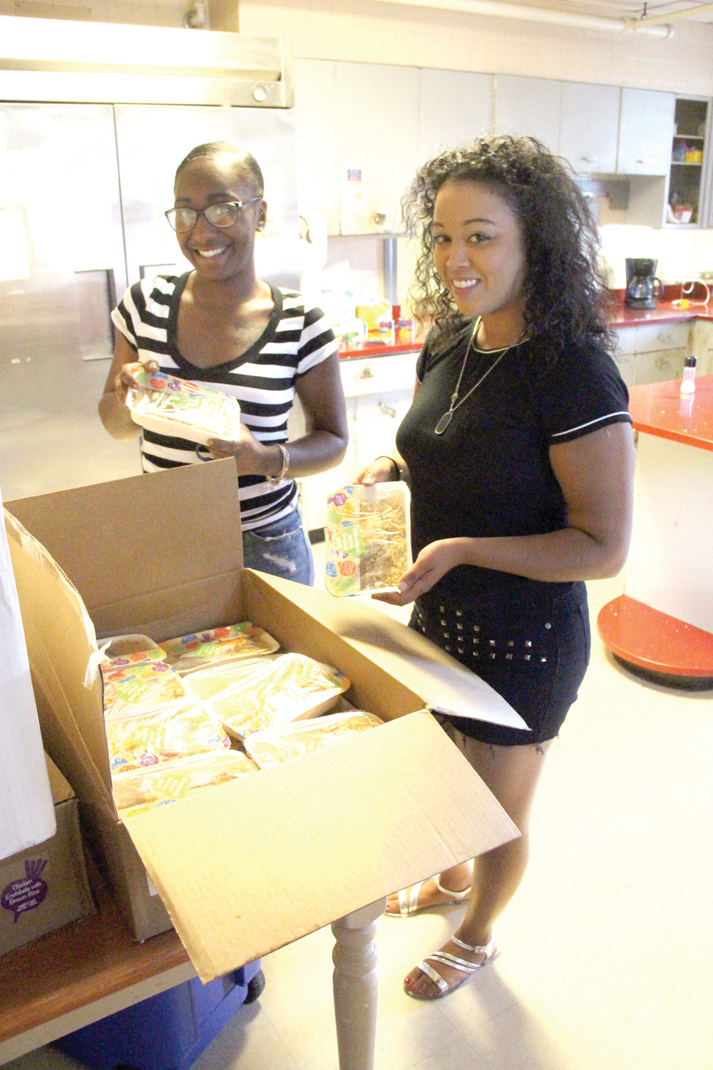 WHAT A SURPRISE: Asia Maynard and Ariel Martinez of the Crossroads-run Warwick Family Shelter in Conimicut look over some of the ready-to-cook meals delivered to the shelter.