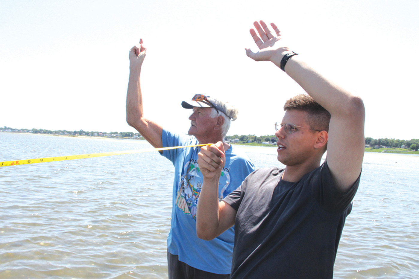 TO THE EAST: Ray Turbitt and Shane Bonin signal to team members to head southeast as they mark off a quadrant.