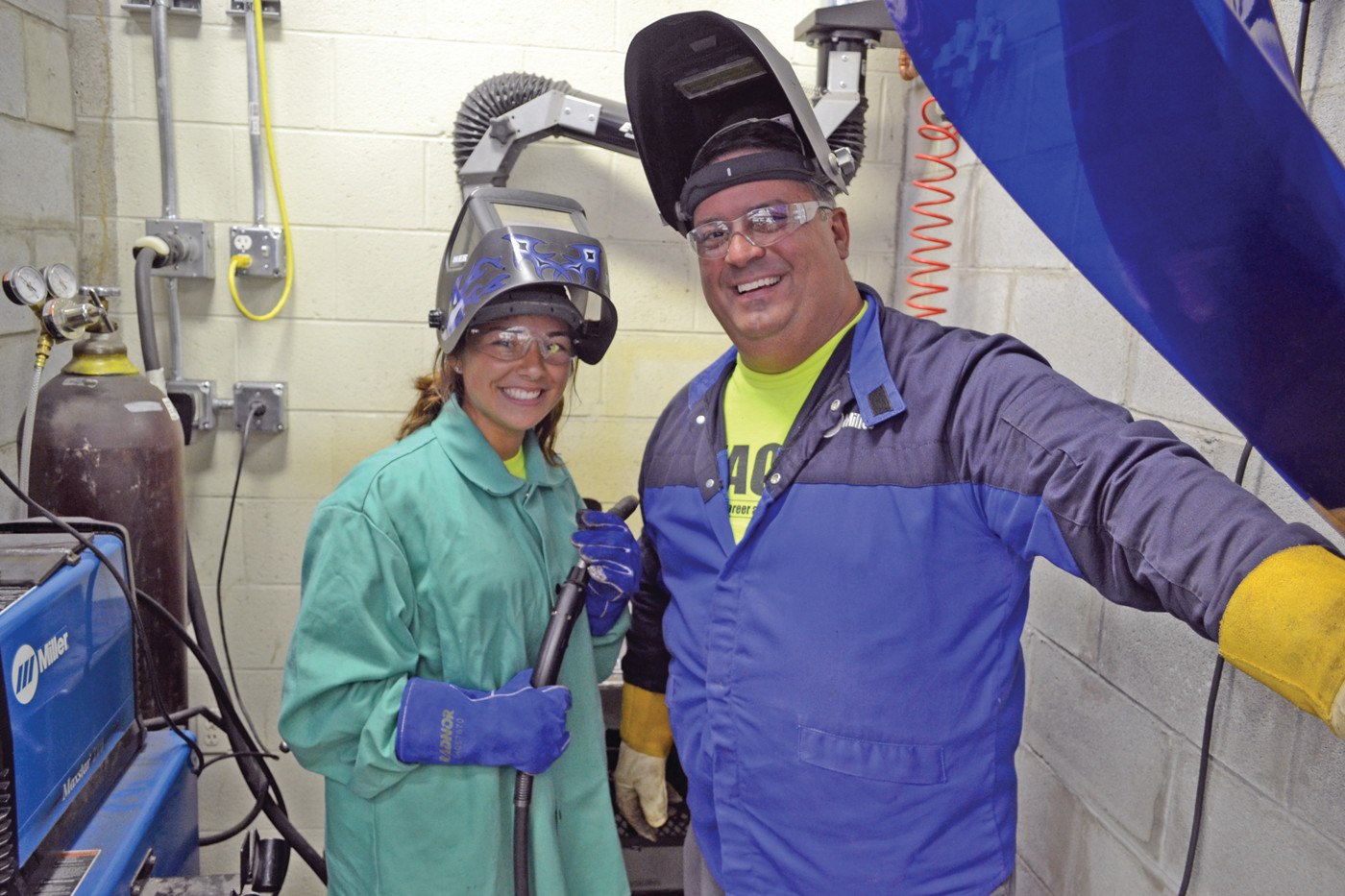 SOMETHING DIFFERENT: Mae D'Ambra smiles in her welding gear prior to welding her name into a piece of metal she cut out and de-burred to smooth its edges. She said she never expected to be doing such an activity. Also pictured is instructor Chris Bianco.