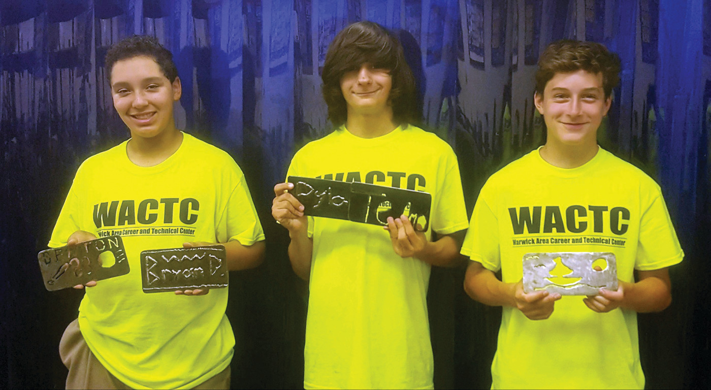 MAKING THE CUT: From left to right, Bryan Denton, Dylan Mendes and Owen Dean hold up their finished creations made from utilizing a laser cutter, which melted shapes of their design out of metal they cut themselves.