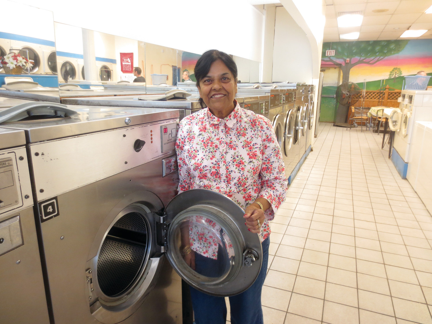 Kaushal Jain is a familiar face at the family-owned business that she and her husband have operated for over twenty-five years ~ here, she is ready to fold a load of clothes, straight from one of the laundromat's modern dryers.