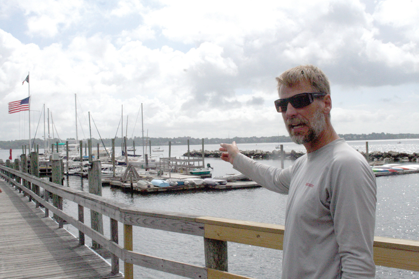 HIS DOMAIN: Chris Krane, who has run the Edgewood Yacht Club youth sailing school for the past 14 years, points to the dock where they keep most of their boats.