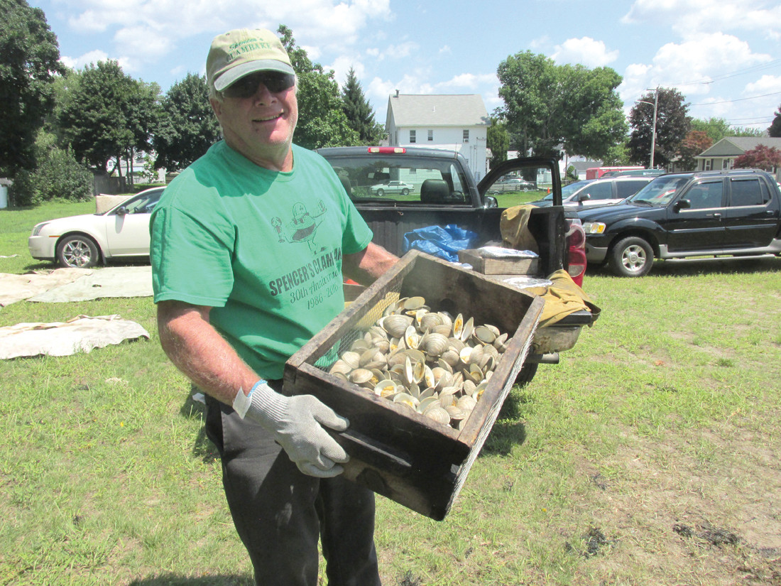AWESOME APPETIZER: Byron Kee, a staffer for Spencer's Clambakes, holds a wooden container full of steamed little necks in the shell that people enjoyed once topped with melted butter during Sunday's OLG clambake.