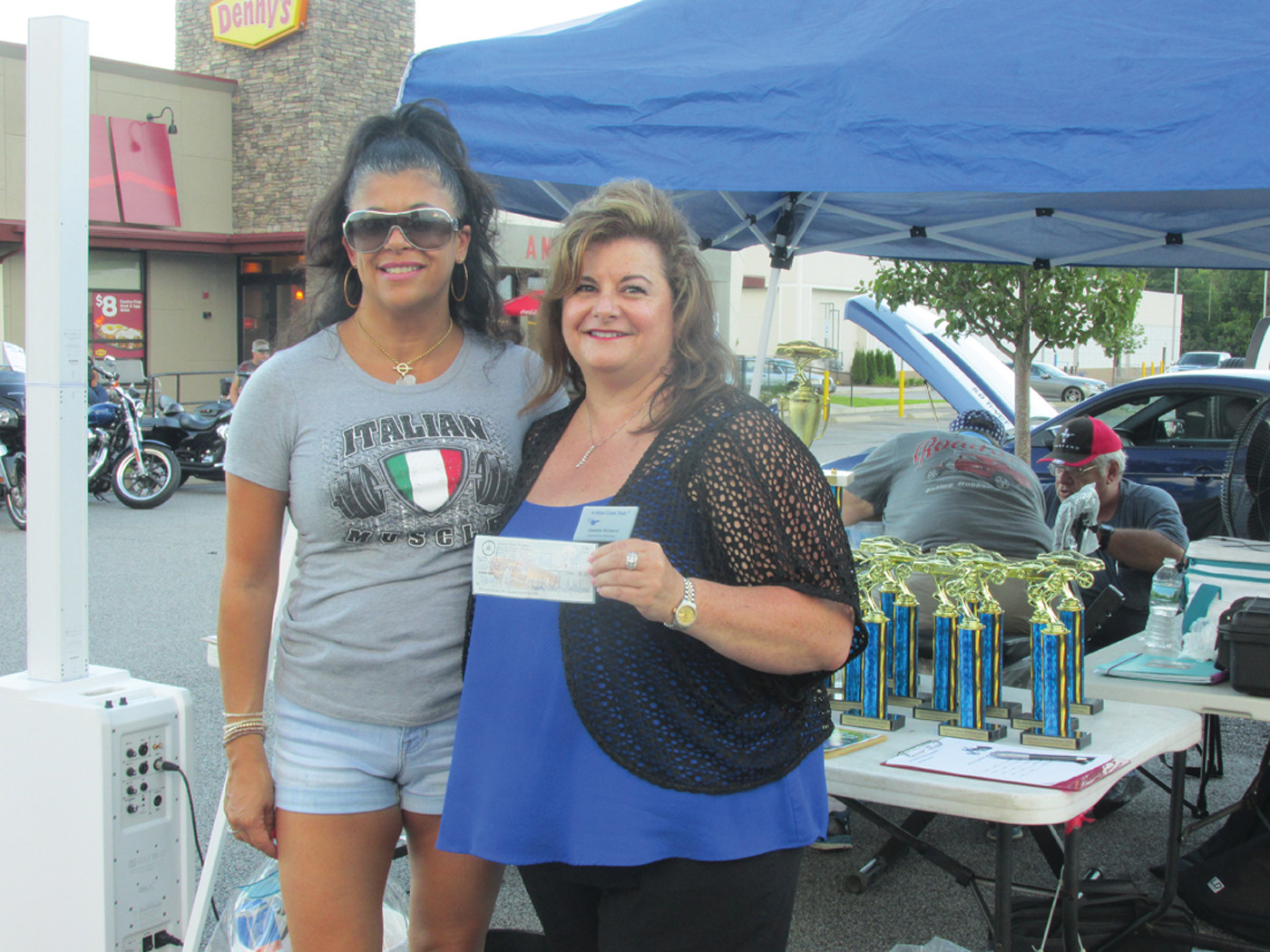 GENEROUS GIFT: Gina Sabitoni-Arakelian (left), treasurer and co-found of the Johnston Street Machines, gives A Wish Come True Operations Manager Debbie Richard a check.
