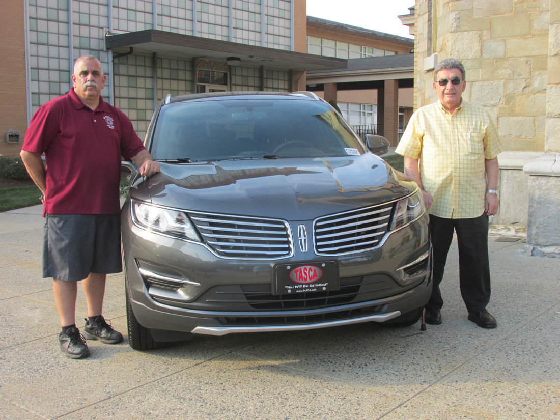 PERFECT PRIZE: Saint Rocco's Church Feast and Festival Co-chairmen Richard Montella (left) and John Ricci (right) stand beside this 2018 Lincoln MKC that is the Grand Prize in the event's annual Grand Raffle Drawing. (Sun Rise photo by Pete Fontaine)