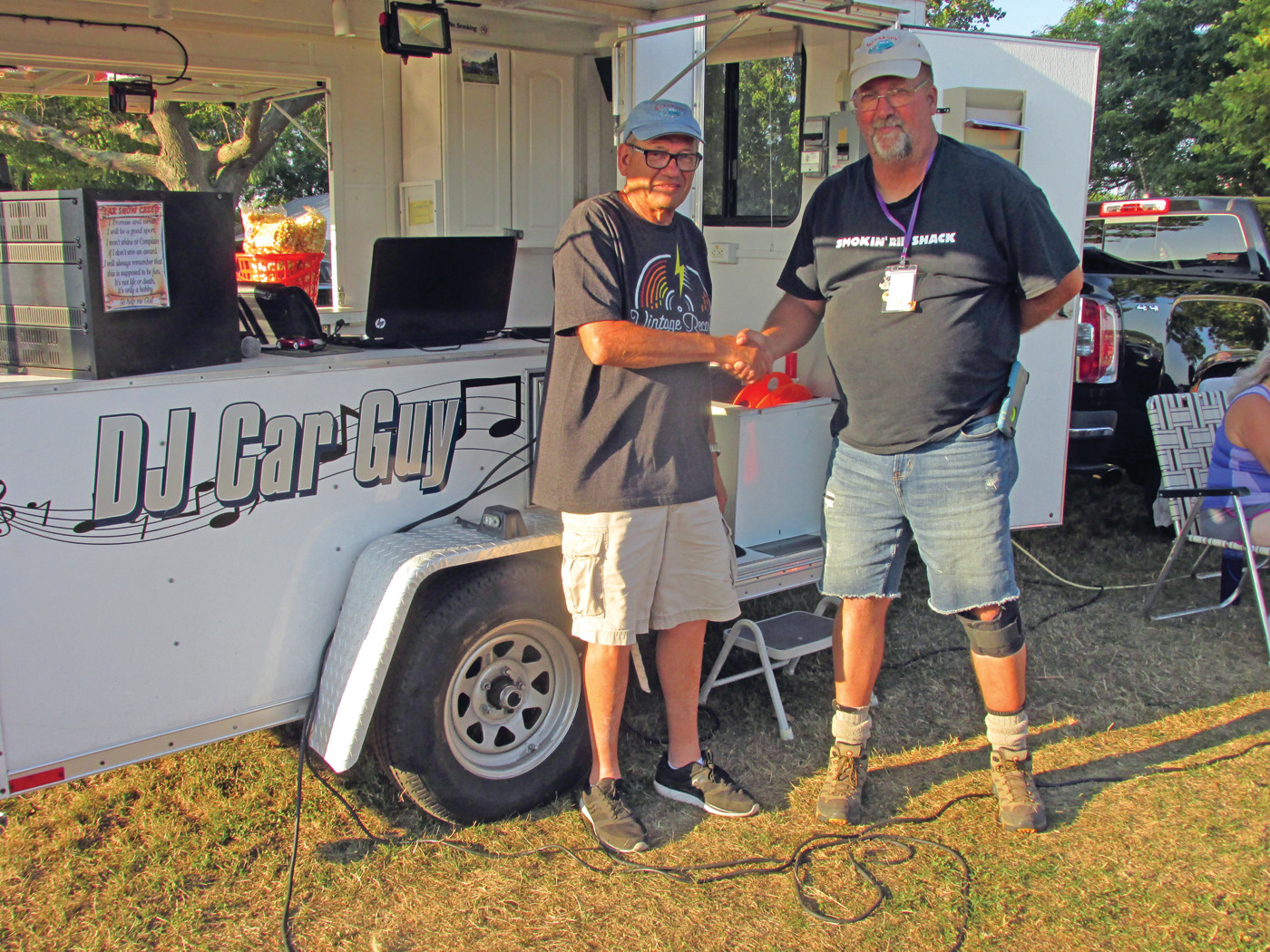 "CRUISE CREW: Richard George (left) gets a special ""Thank You"" handshake from Jason Hill, president of the Warwick Lions Club, for agreeing to supply special music for Saturday's Cruising at the Crowne Car Show."