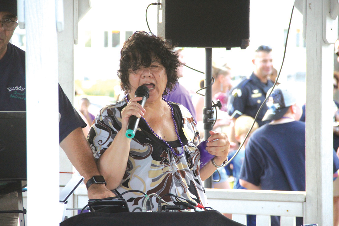 NO, SHE WASN'T SINGING: Ward 6 Councilwoman Donna Travis, who has spearheaded the National Night Out program with Warwick Police for years, takes the microphone to announce events.