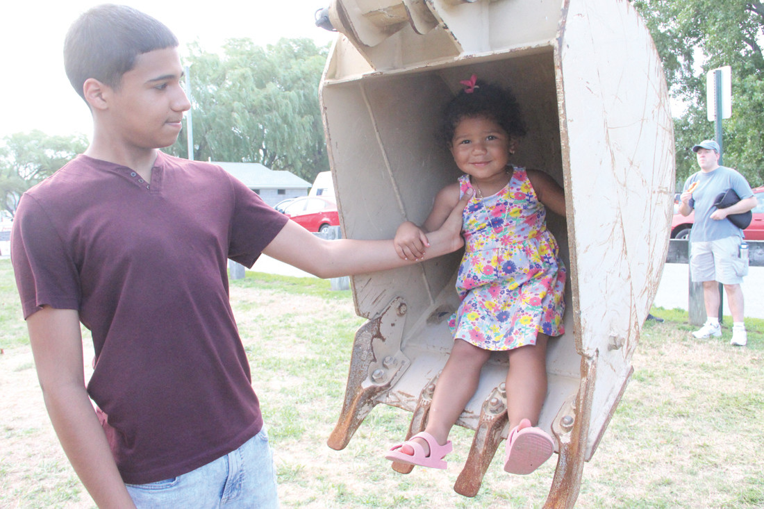A SHOVEL FULL: Zailah Maldonado gets a secure hand from her cousin Edwin Bercian in the scoop of a RI National Guard vehicle.
