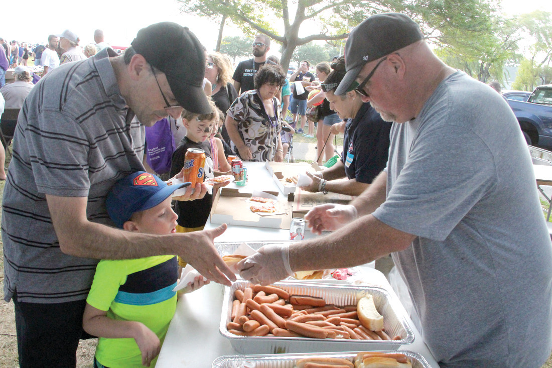 LOTS OF TAKERS: Rob Farrell serves up hot dogs to a hungry crowd.