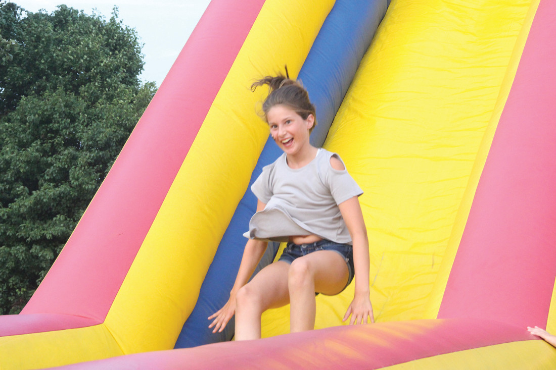 SLIDING WITH A SMILE: Maddie Gautieri rode the bouncing slide again and again.