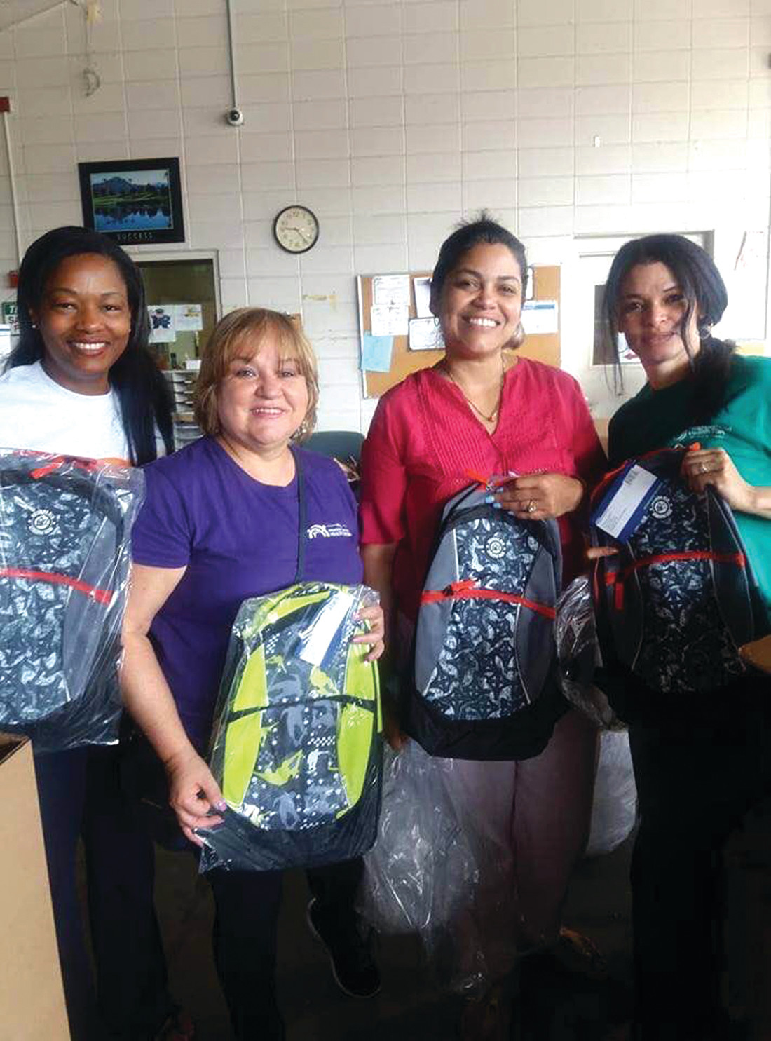 BACKPACK DELIVERY: From left to right, Grace González and Doris De Los Santos (members of the organization Executive Board) and Adriana Vargas and Obed Papp, from the Providence Health Centers Association and the Office of Healthy Communities. The picture was taken during the volunteer packing day the organization hosted in July to stuff the backpacks with school supplies that will be distributed.