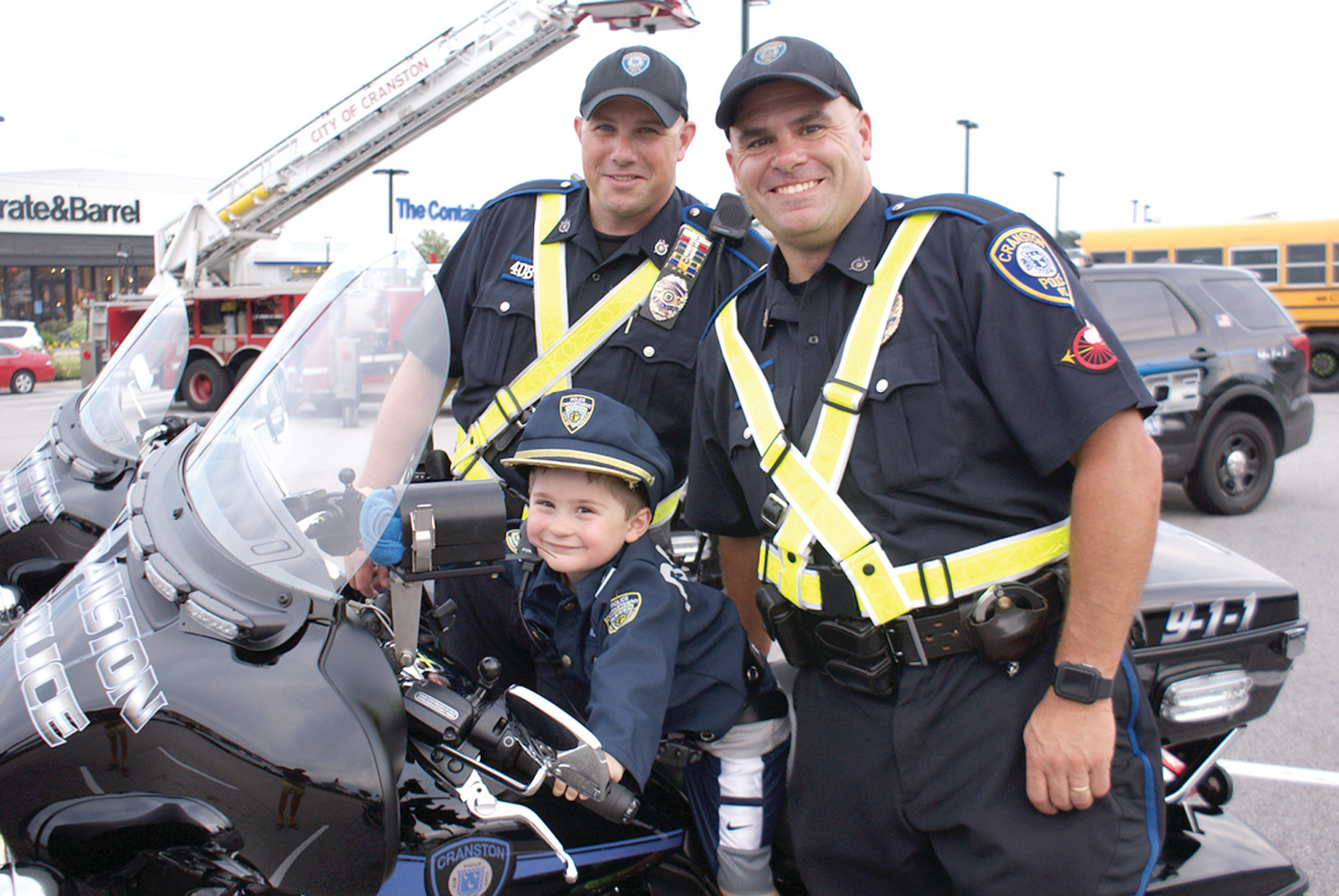 """TRAINEE"": Matthew Mazzola, age 3, enjoyed his time on a Cranston Police Department motorcycle during National Night Out in Garden City as Inspectors Andrew DeCosta and Peter Leclerc stand by him."