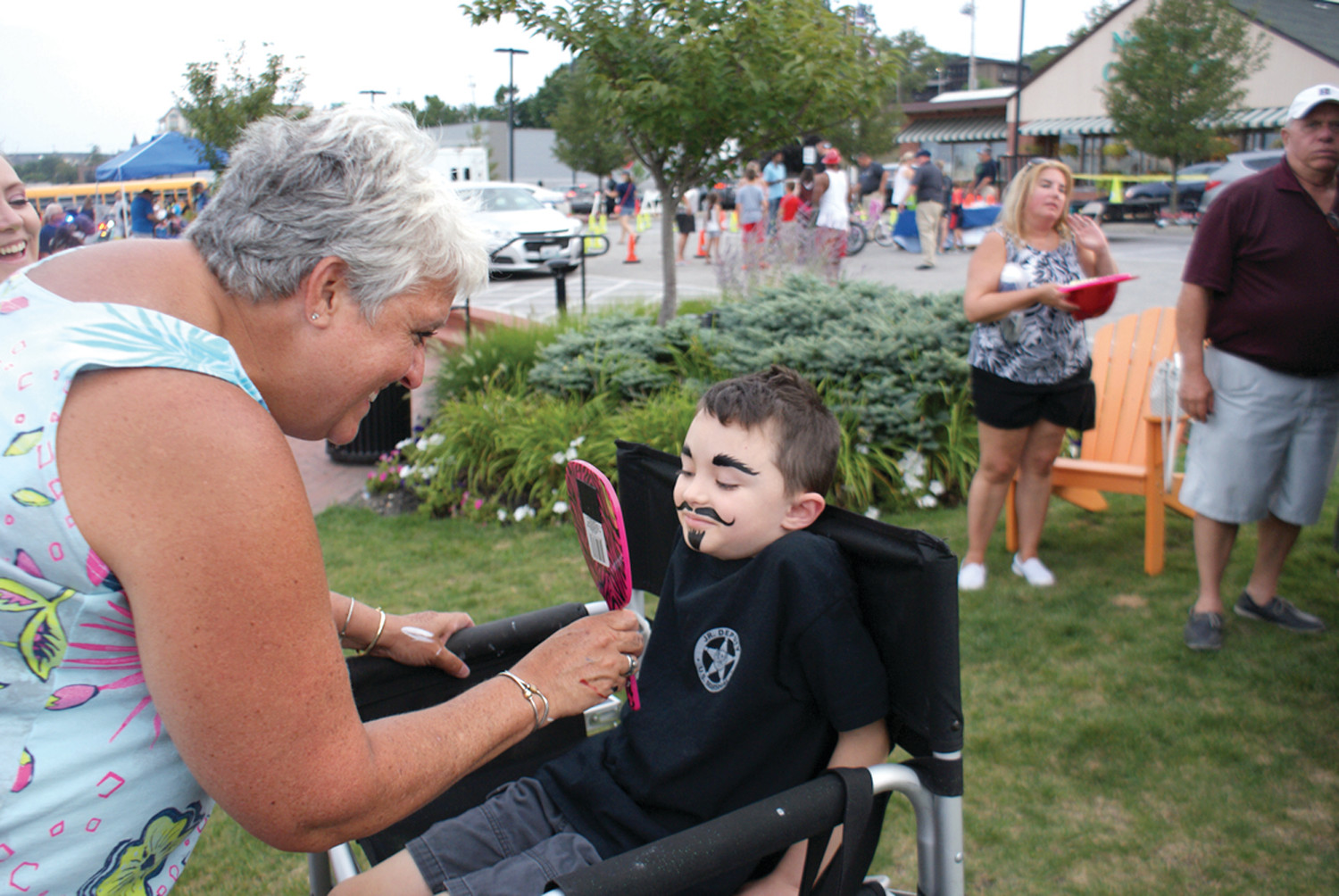 FACE ART: Toni Andersen a face painter from Wow Face Art showed Daniel Treglia, age 6, her completed artwork during National Police Night Out in Garden City Center.
