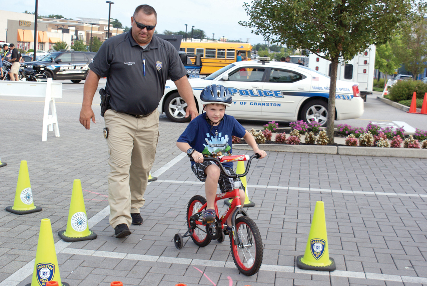 ON THE COURSE: Cranston Police Officer and SRO Matt Davis assisted Norman Trott, age 9, on the bicycle obstacle course set up during National Police Night Out on Aug. 7 in Garden City.
