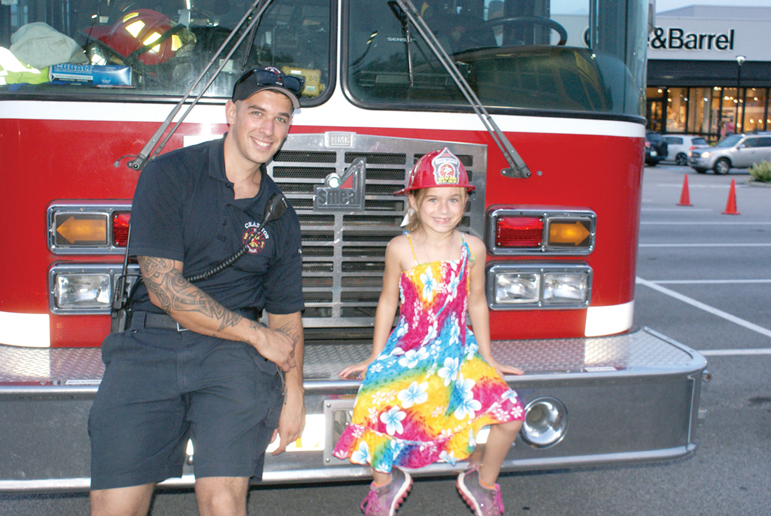 NEW FRIENDS: Cranston Probationary Firefighter Bryan Wall from the Garden City Fire Station enjoyed making a new friend in Gianna Carrara, age 7, during National Police Night Out as they sat on the bumper of Ladder 2.
