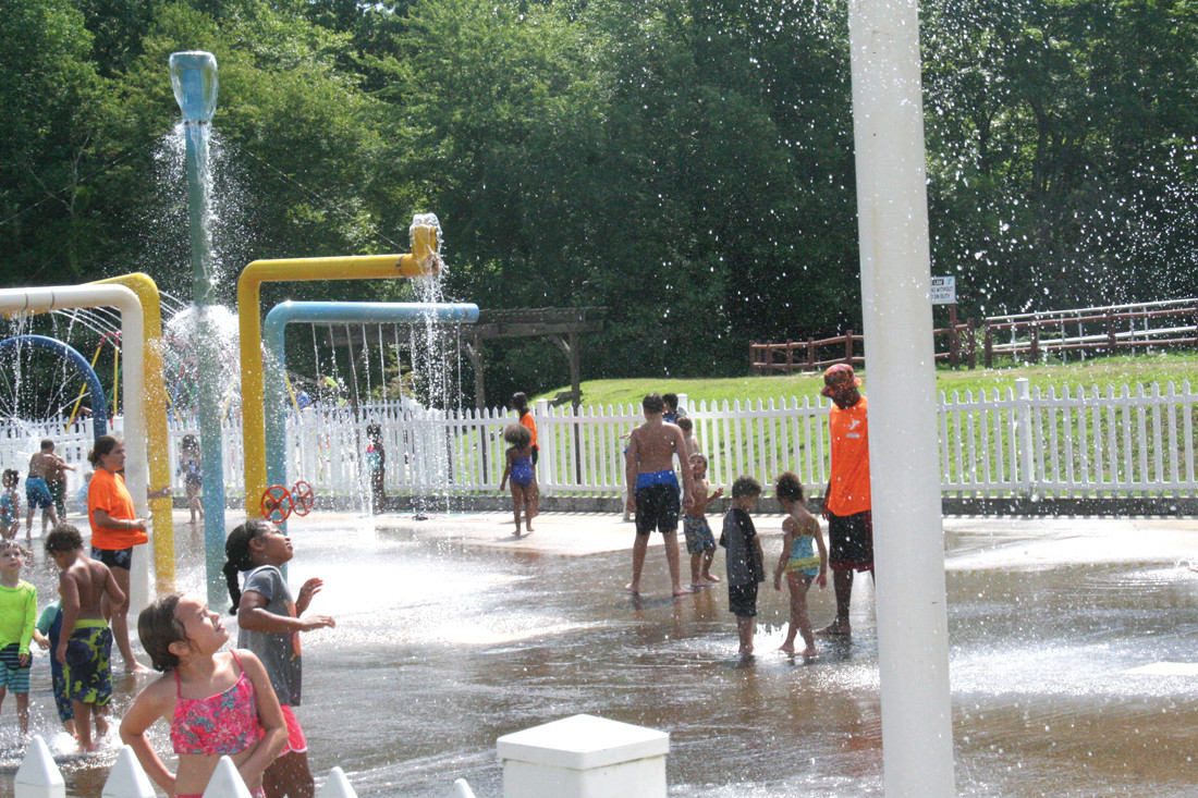 MAKING A SPLASH: Camp members and counselors enjoy the cool water in Camp OK-WA-NESSETT's 'splash zone' during a hot August morning yesterday.