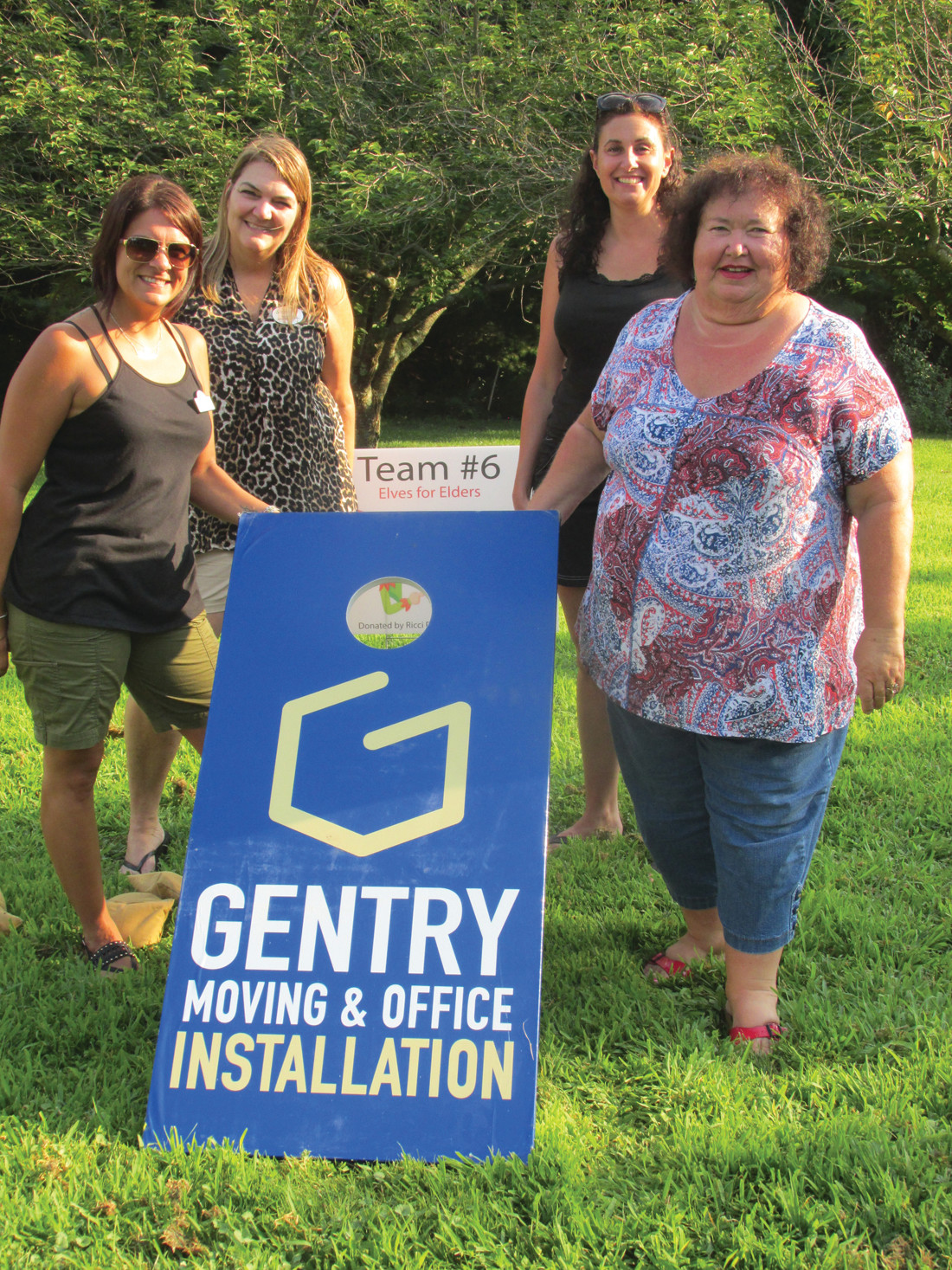 CRUM'S CREW: Gentry Moving & Storage was the proud sponsor of this board featured in last week's cornhole game that netted $808 for Elves for Elders. Players in the 20-team field included Jen Burns, Tracy Cale, Christine Crum and Maxine Hutchins. (Sun Rise photos by Pete Fontaine)