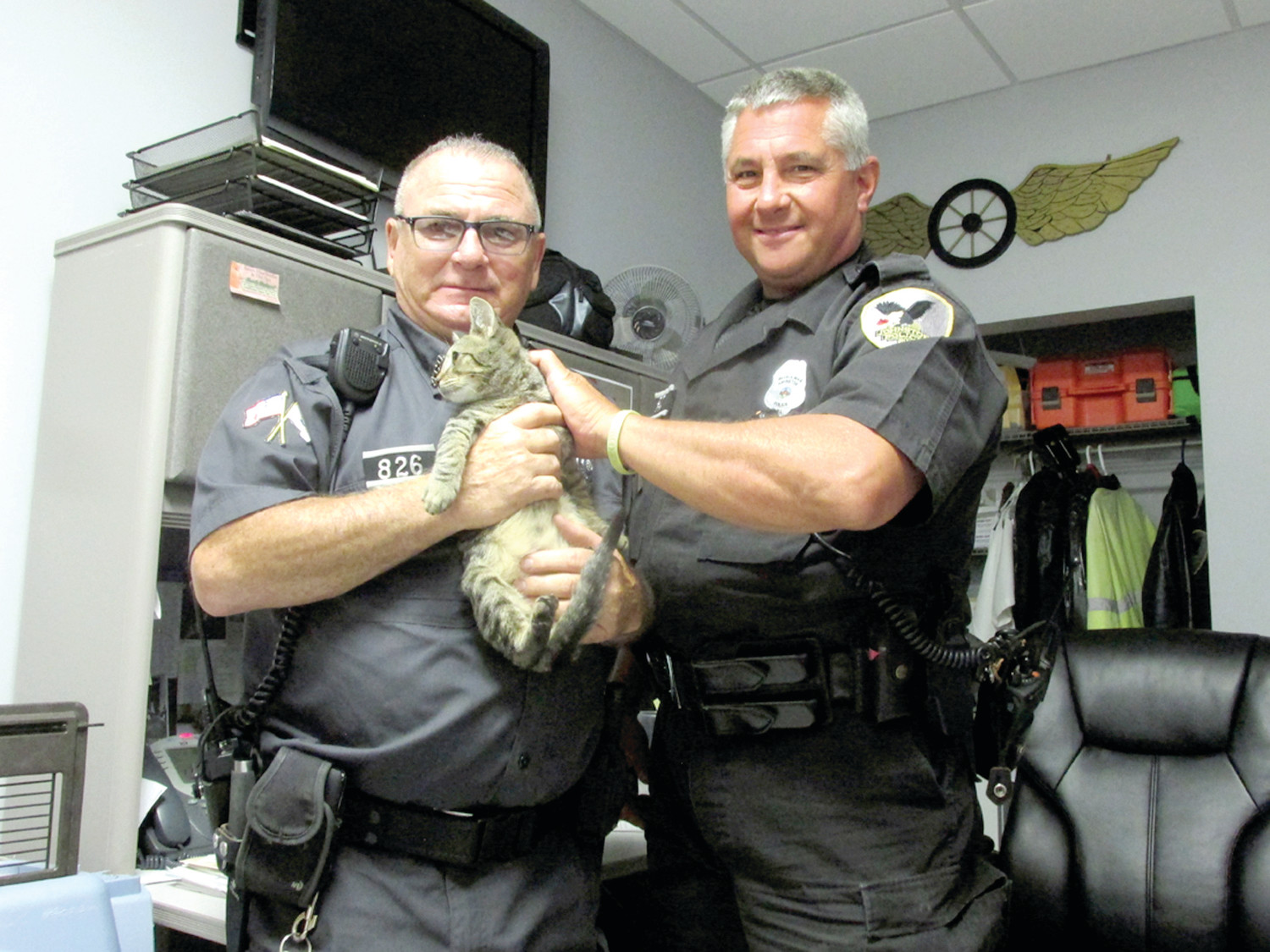 LANDED LOVERS: Johnston Animal Control Officer Richard Starnino holds Landed, who with help from veterinarians at the Ferguson Animal Hospital he brought back to life almost being dead, as Patrolman David Slinko looks on while explaining the unique story and that they're seeking a home for the tiny Tiger cat. (Sun Rise photo by Pete Fontaine)