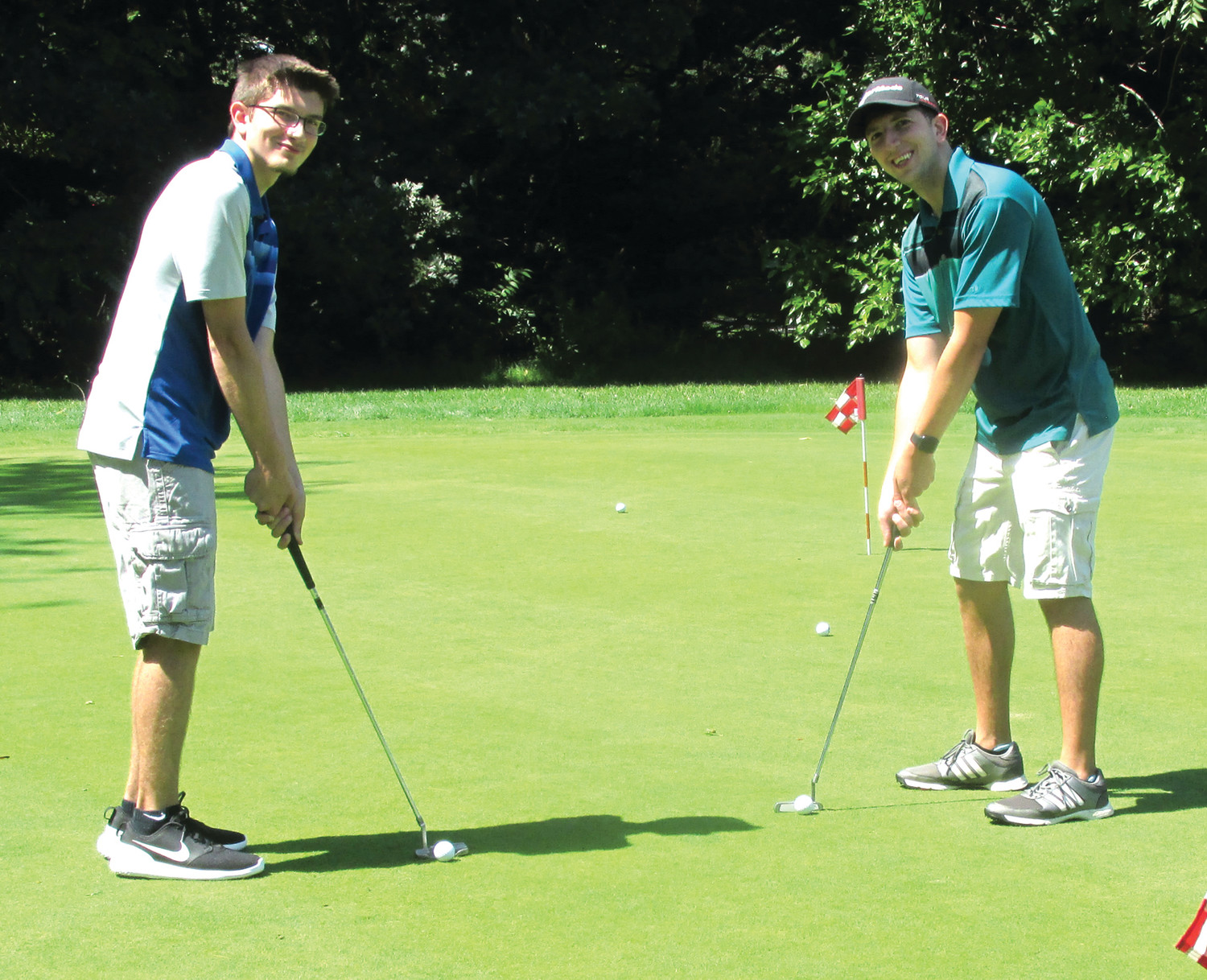 PERFECT PUTTS: Jordon Oliveira (left), a junior at JHS and Josh Oliveira, Class of 2012, enjoy a lighter moment on the putting greet at Triggs Memorial Golf Course before playing in the first ever Panther Gridiron Club tourney. Sun Rise photos by Pete Fontaine