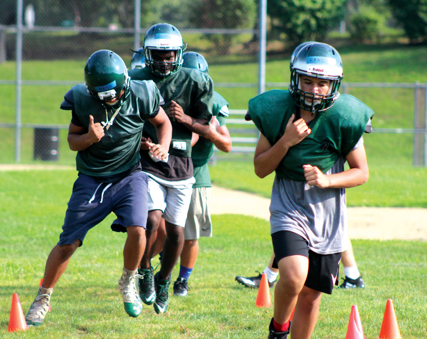 DOG DAYS OF CAMP: Running backs from the Cranston East football team run through ball security drills during a practice at the team's preseason training camp at the fields at Bain Middle School.