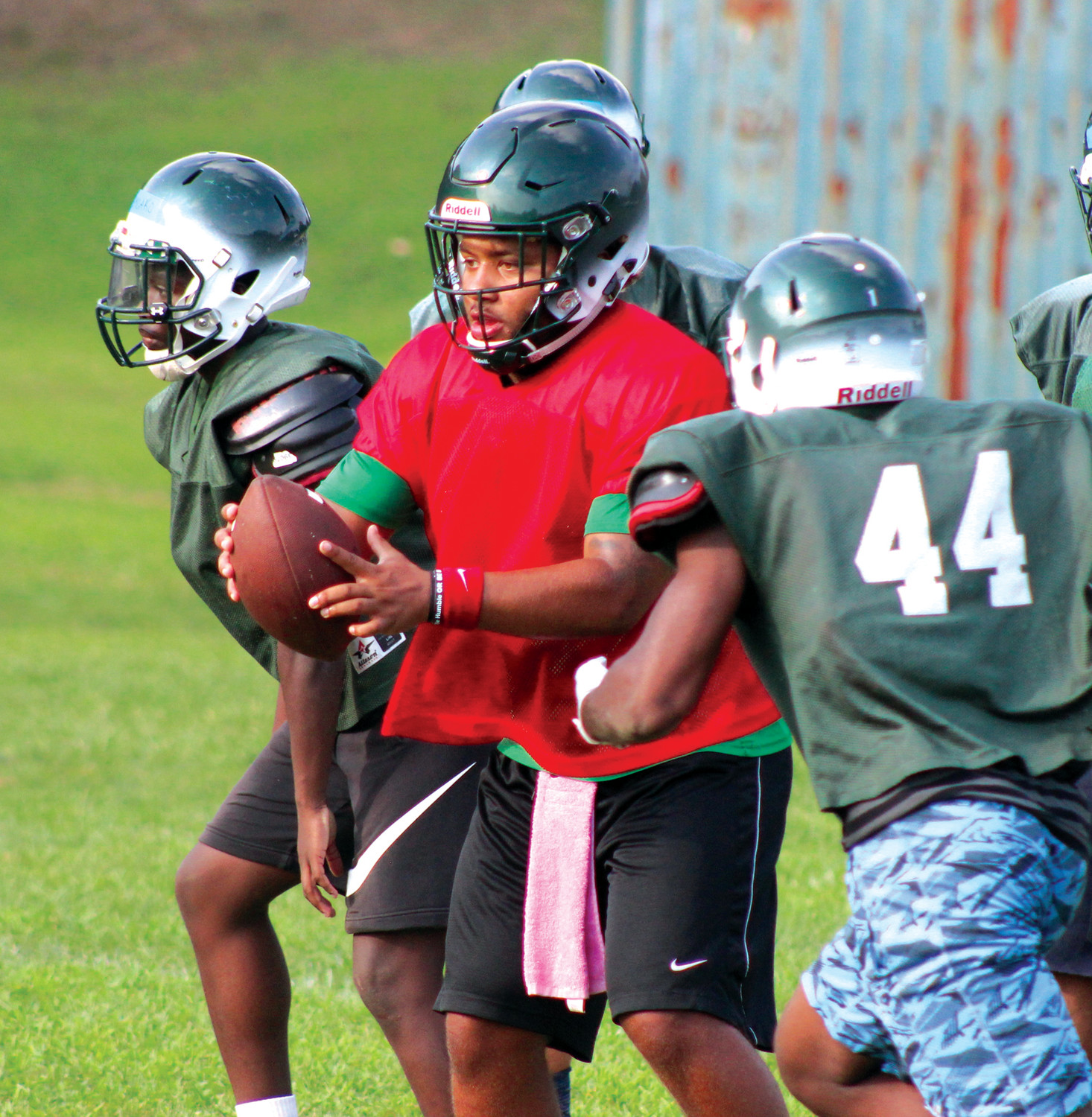 UNDER CENTER: Rayven deOliveira (red) hands off to a running back during a drill at practice. deOliveira is set to replace Justin Neary at quarterback for East.
