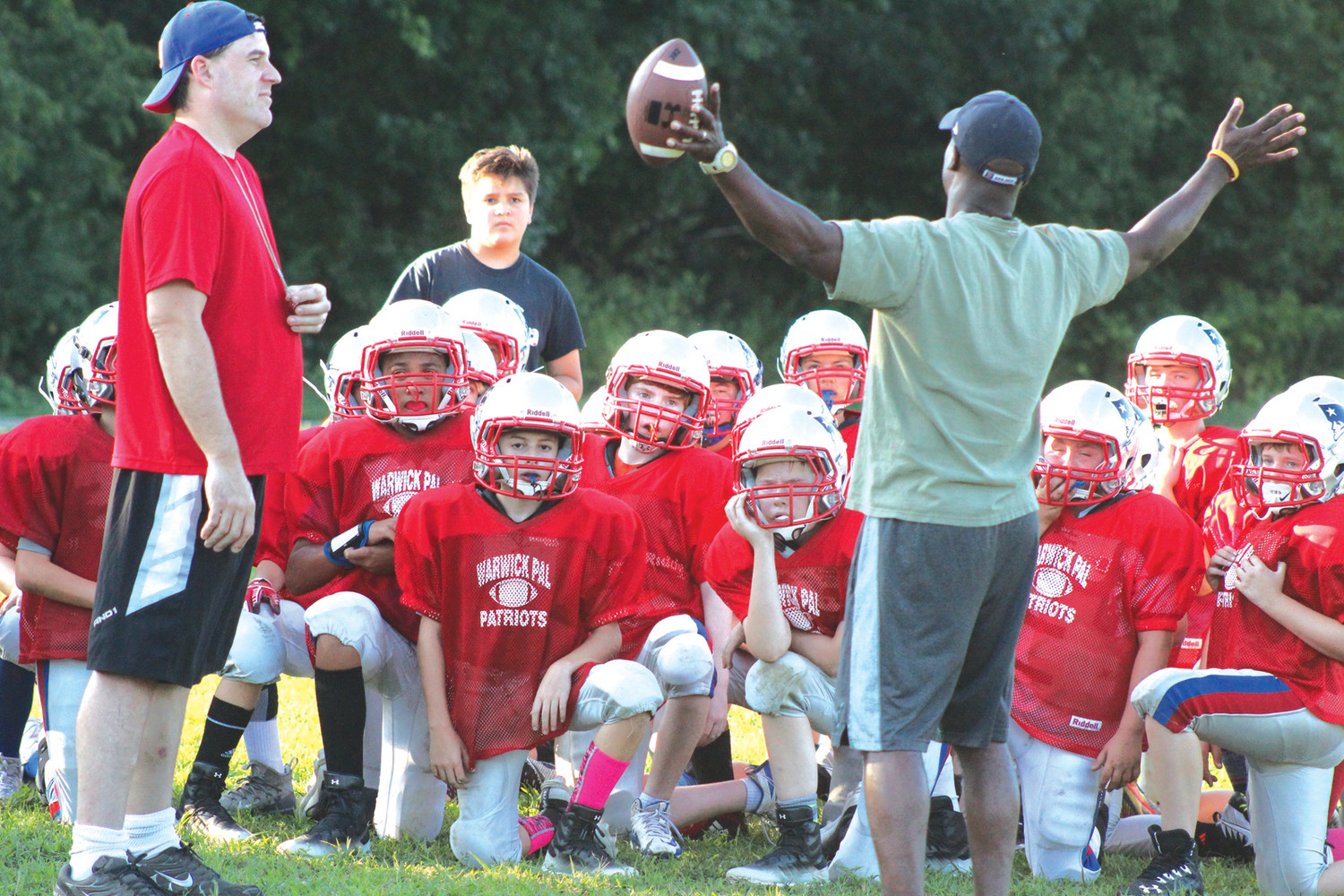 HUDDLE UP: A Warwick Police Athletic League football team listens to a coach's instructions during practice.