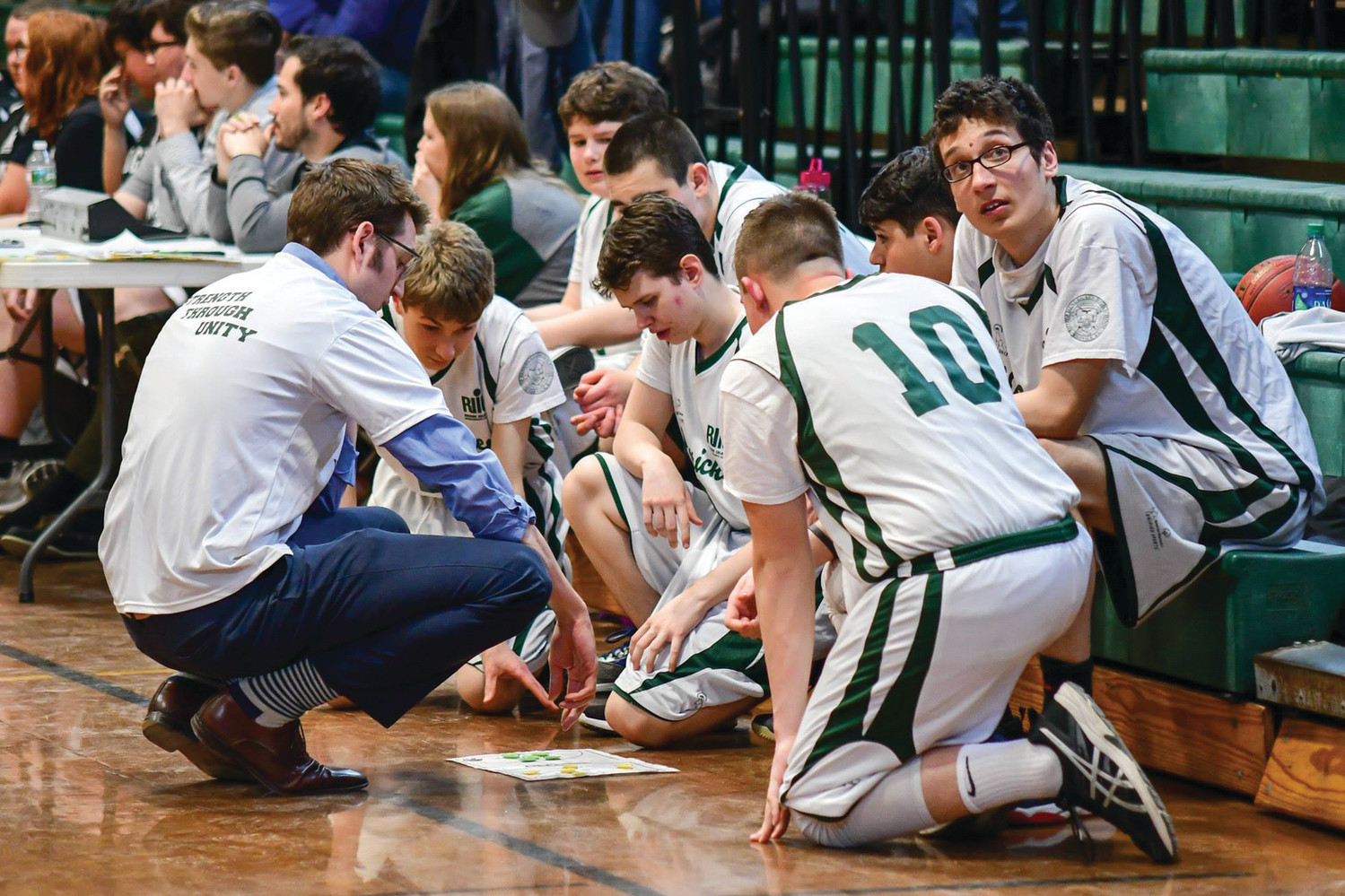 X'S AND O'S: The Bishop Hendricken unified basketball team gathers during a timeout during the 2018 season.