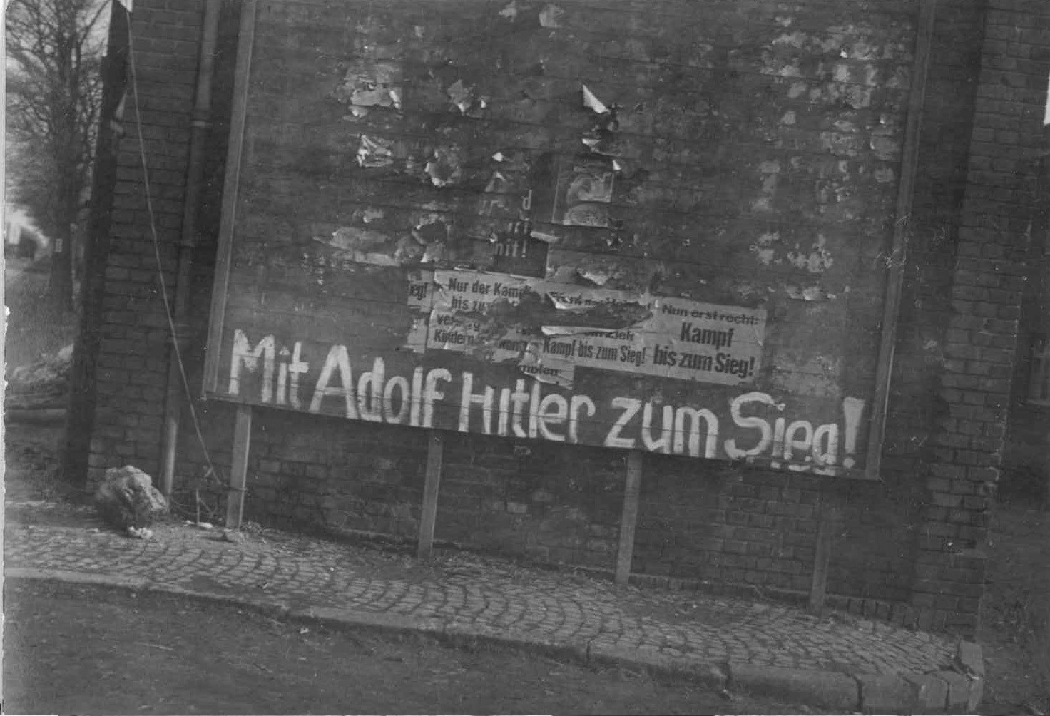 "Graffiti on a building that translates roughly to ""With Hitler for victory"""