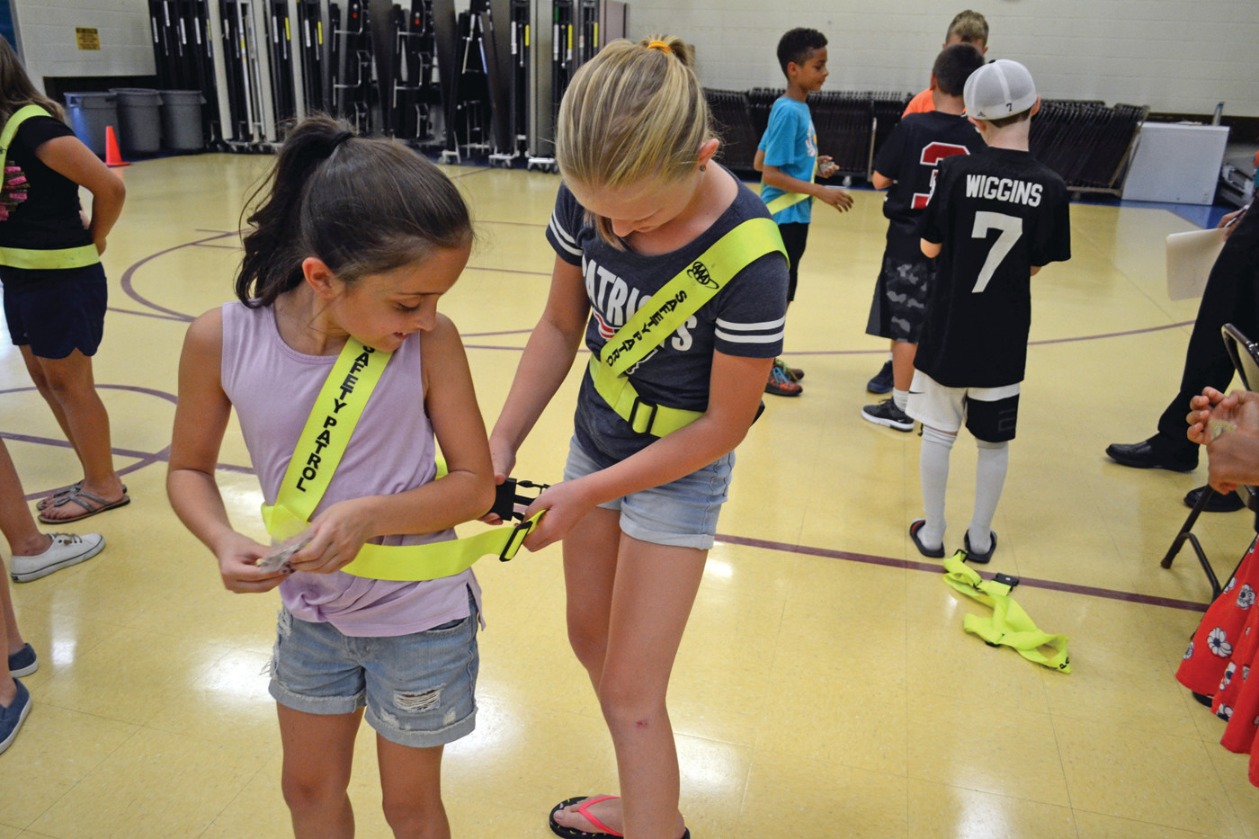 A LITTLE HELP: Cora Miller assists Madeline Pettinicchil secure her safety straps at Hoxsie after the group of 5th graders received their badges as part of the school Safety Patrol.